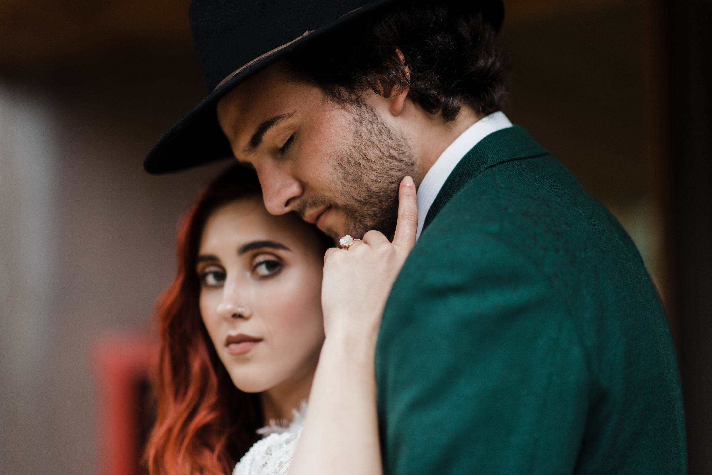 Groom in green jacket and black fedora closes his eyes as bride softly grazes his face with her hand.