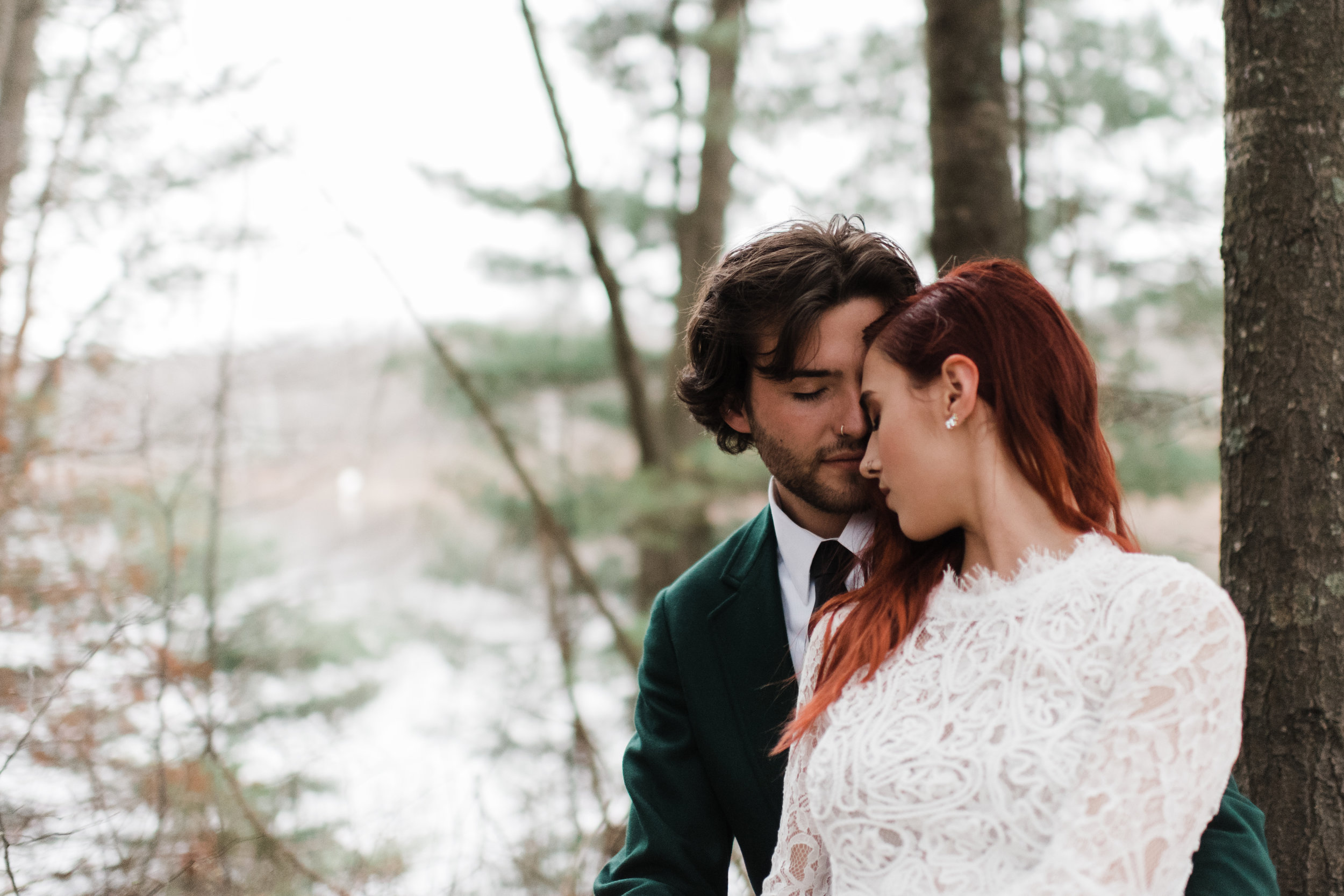 Bride with red hair rests forehead against groom's nose.