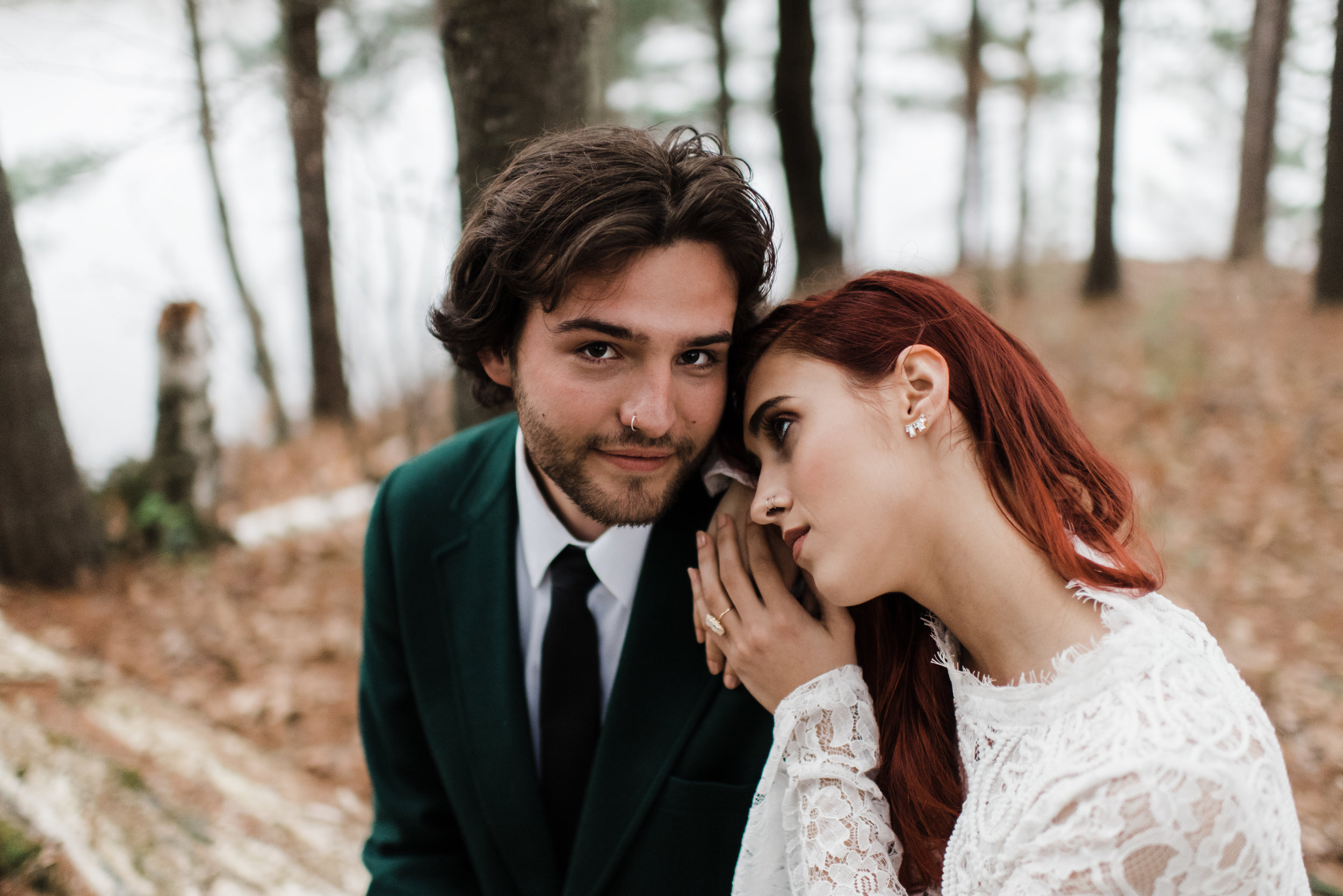 Groom in green jacket smiles as bride in lace and beaded crop top rests her head on his shoulder.