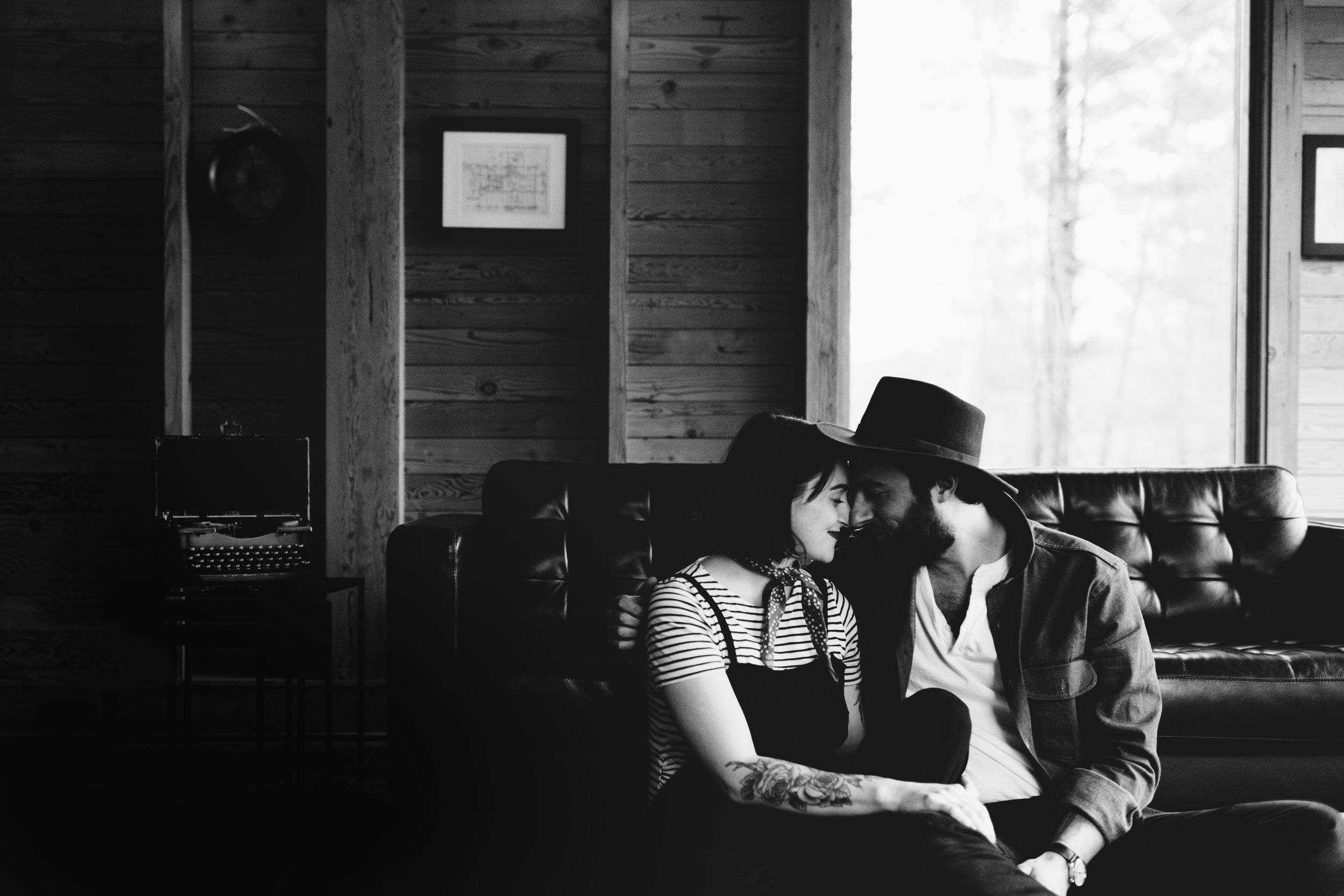Black and white photo of a couple sitting in front of a leather couch at a cabin on Two Bear Lake in Weyerhauser, WI.
