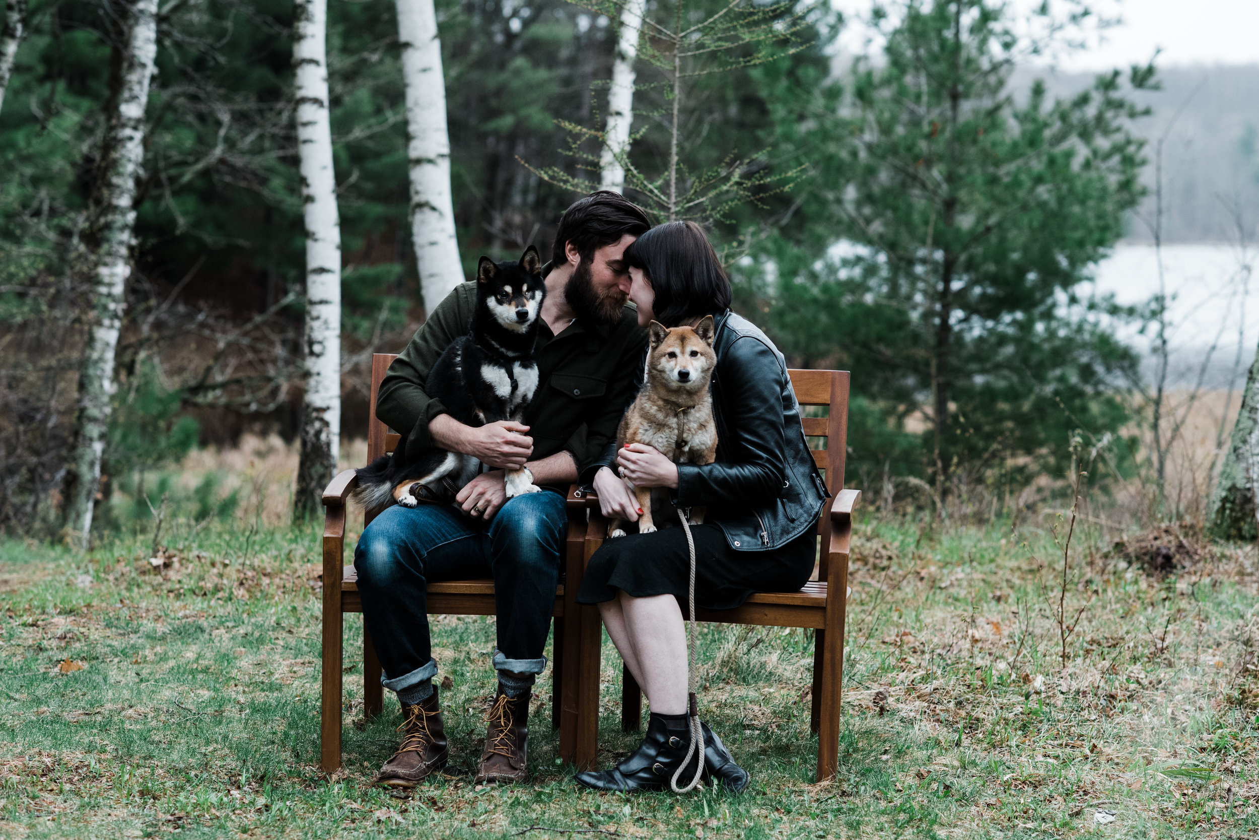Photo of a couple sitting on a bench outside with their dogs at a cabin on Two Bear Lake in Weyerhauser, WI.