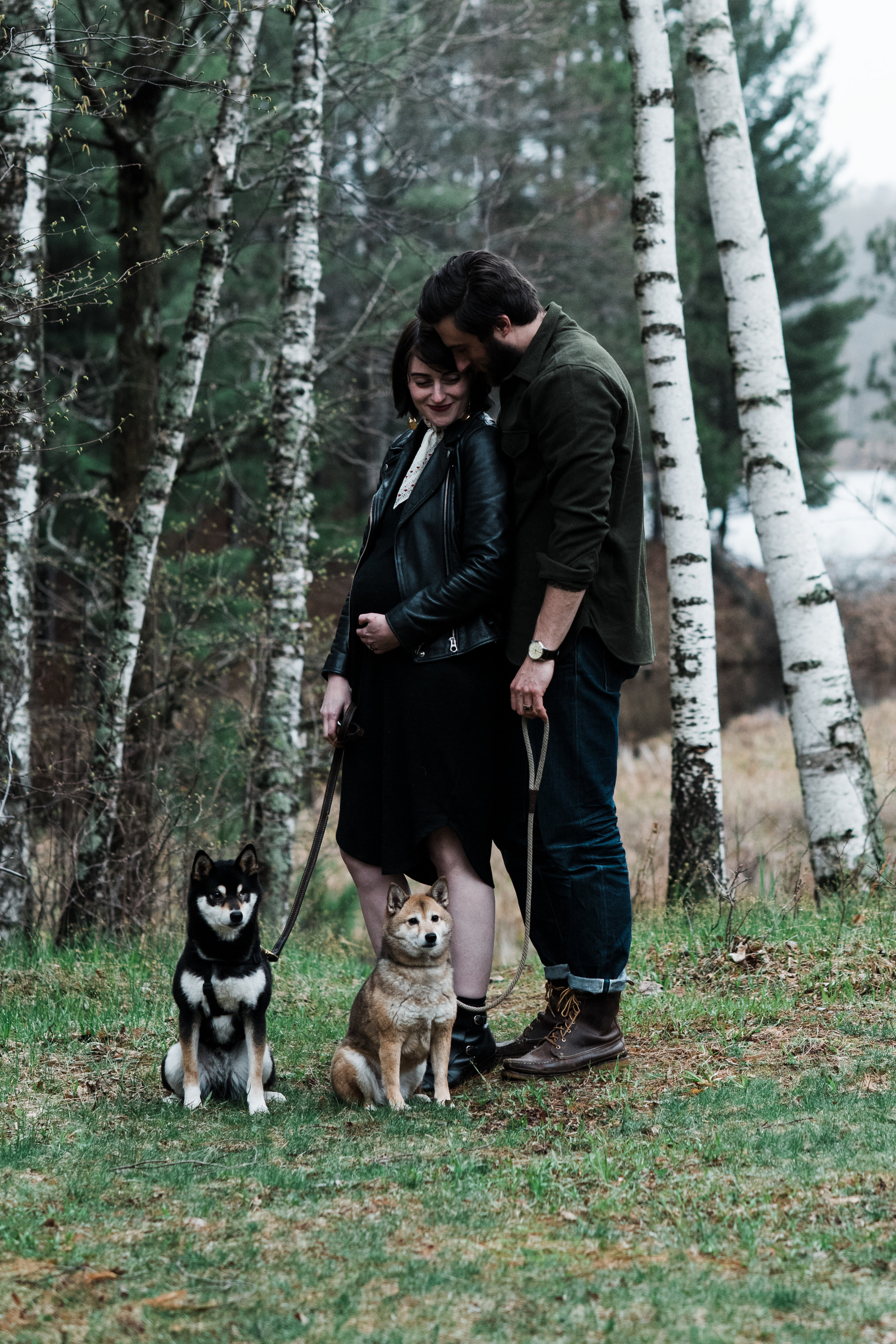 Photo of a couple standing outside by some birch trees with their dogs at a cabin on Two Bear Lake in Weyerhauser, WI.