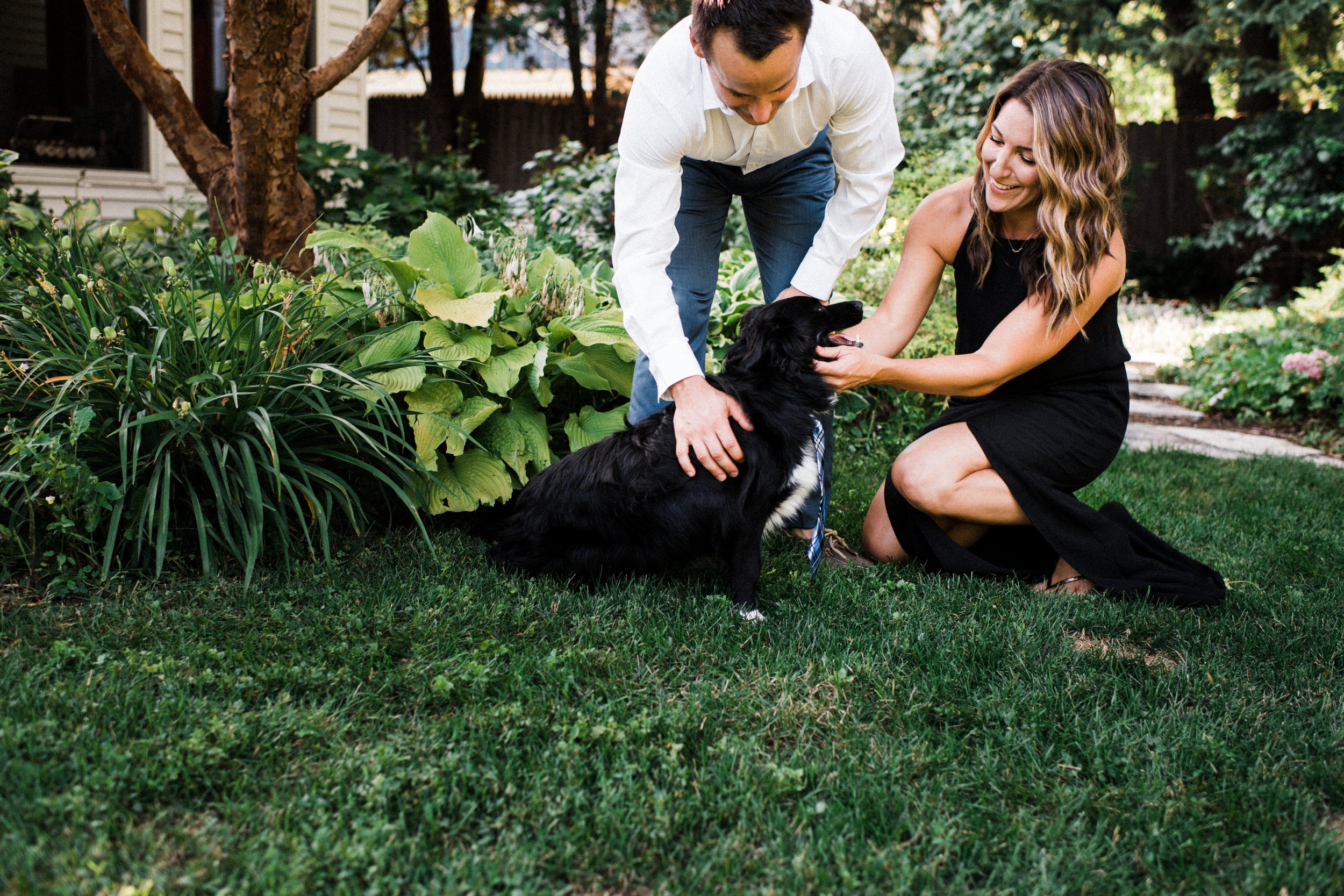 Engaged couple playing with their dog in the backyard.