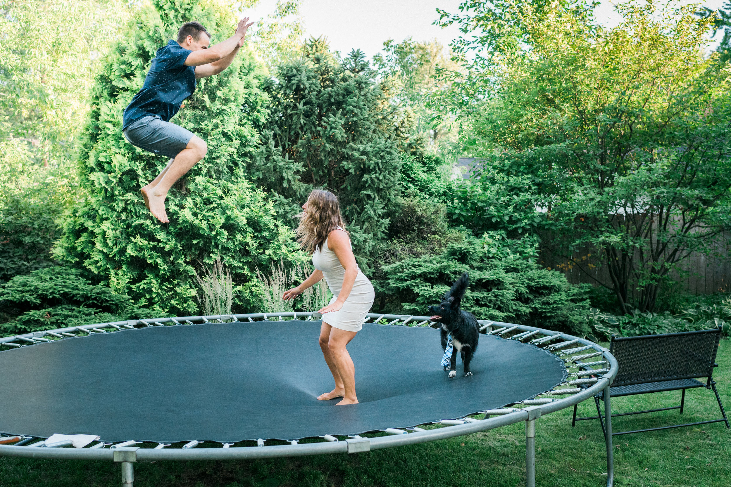 Engaged couple jumping on a trampolin with their dog.