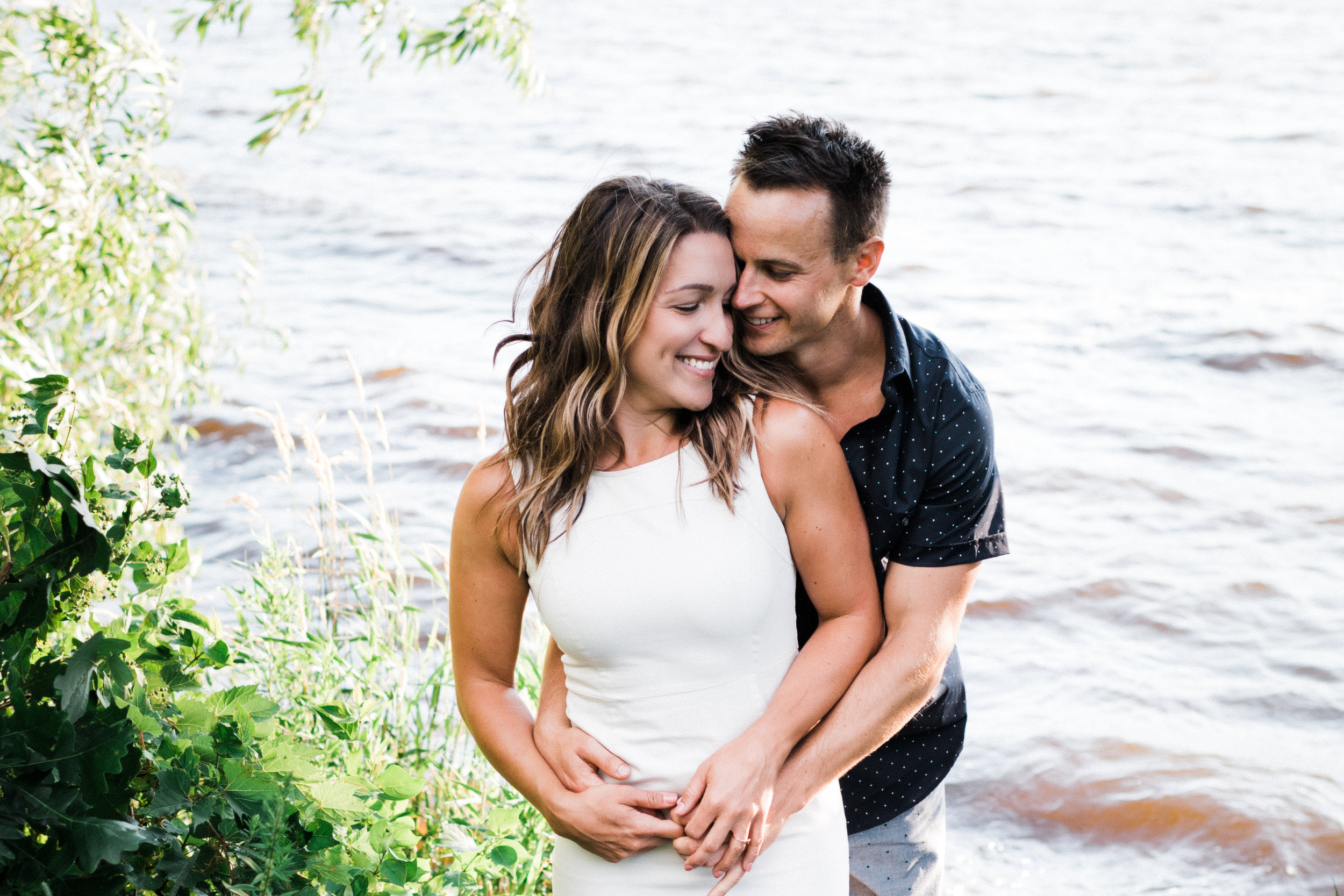Man stands behind his fiancé and holds her by the waist as she smiles.