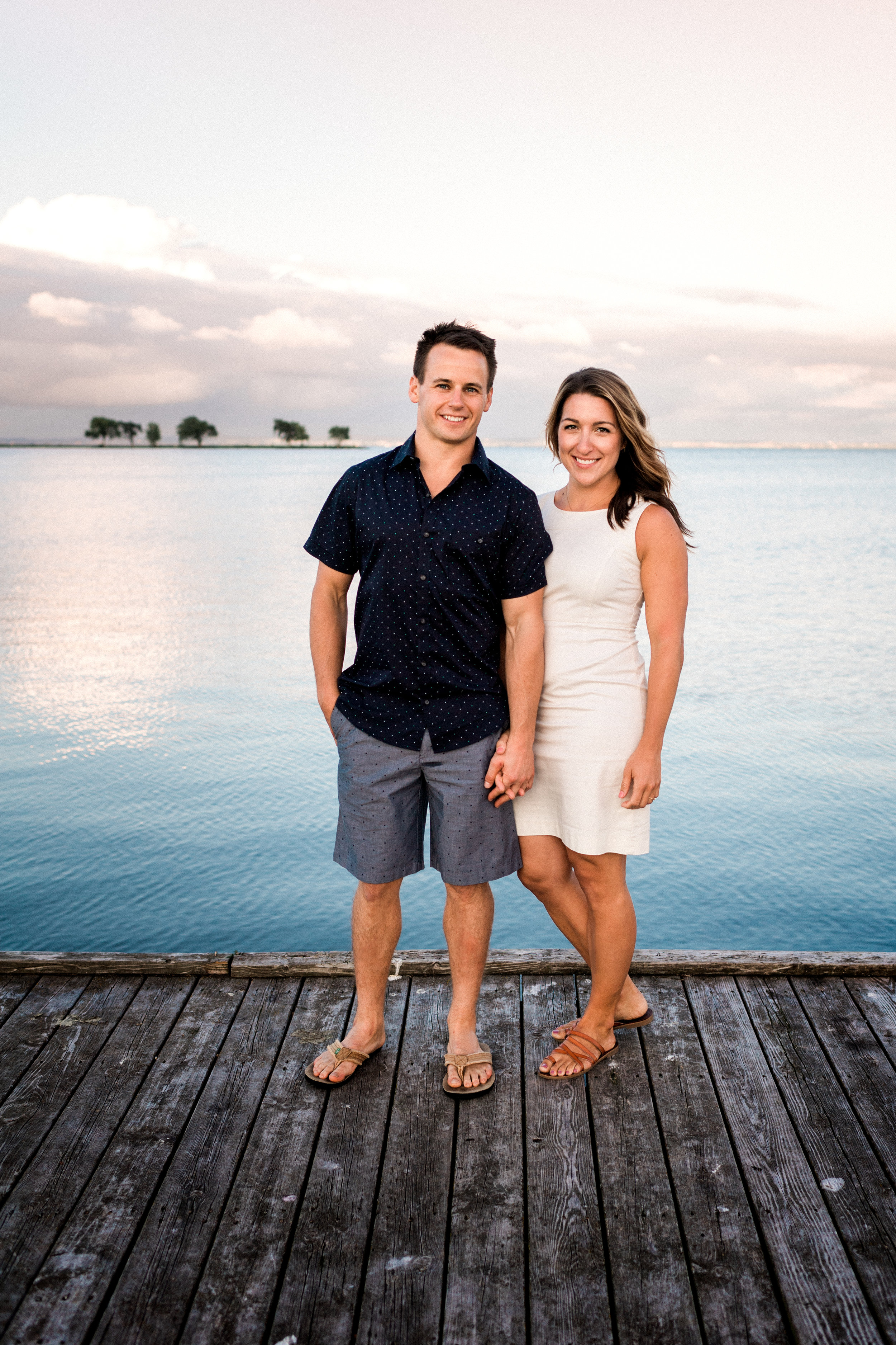 Engaged couple holds hands while standing on a dock.