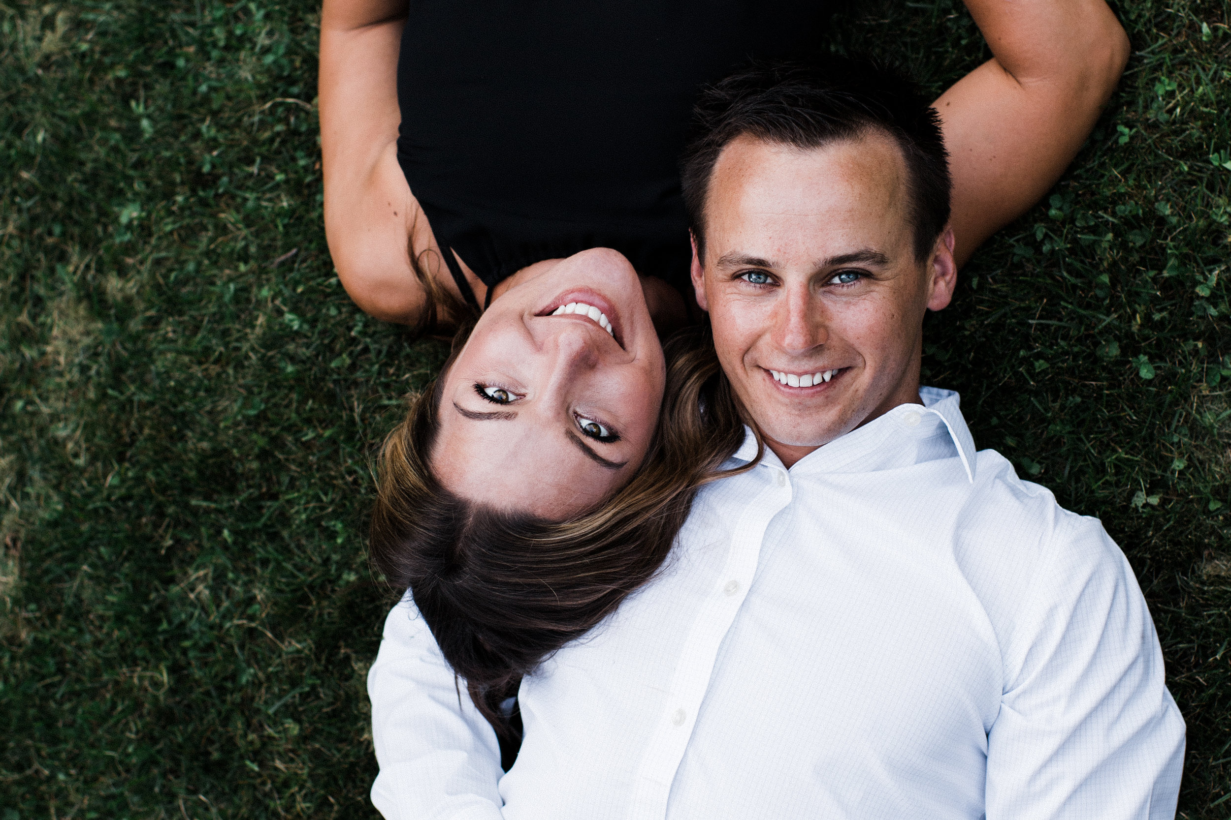 Engaged couple laying in their backyard with heads on each other's shoulders.