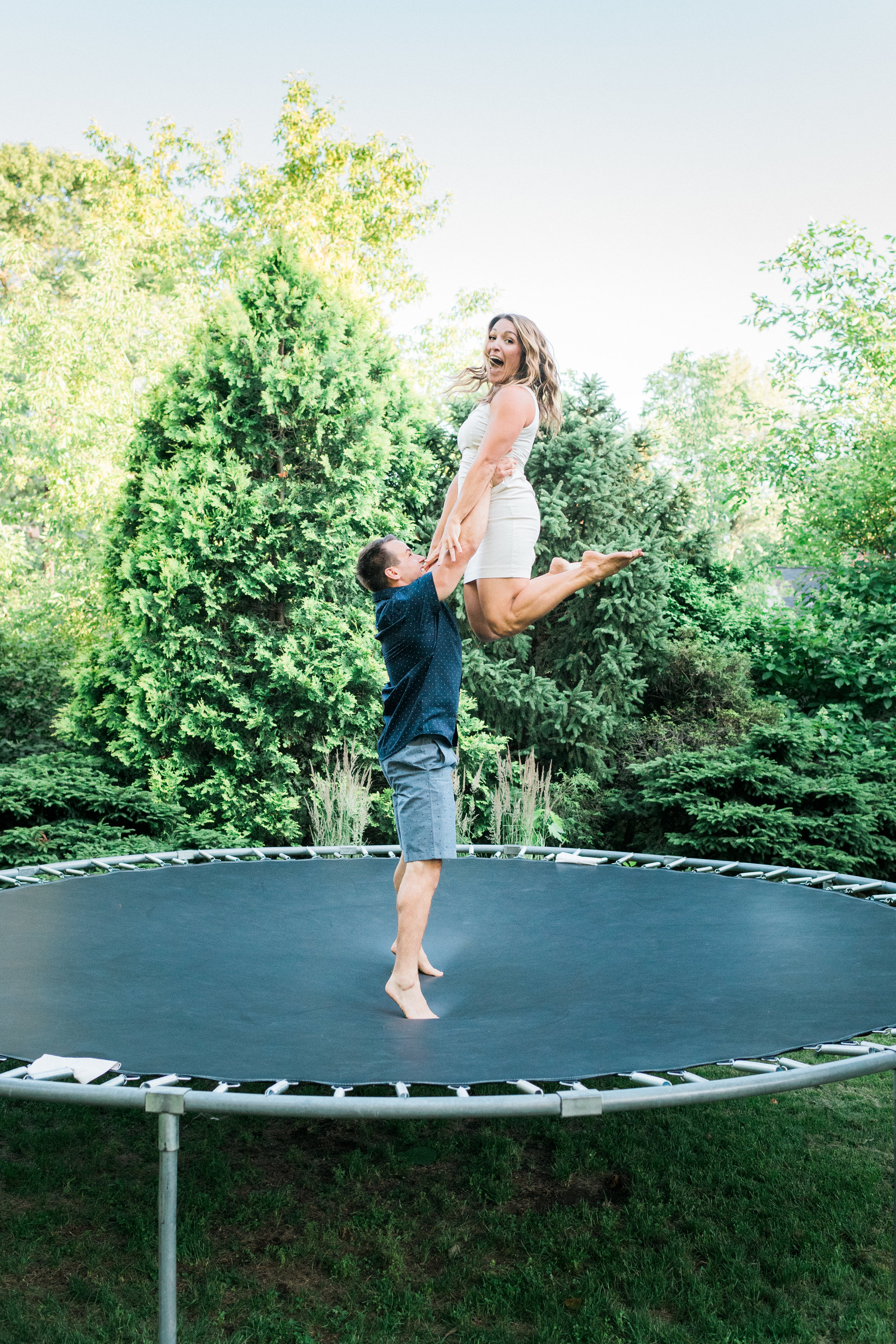 Man on a trampoline lifts his fiancé in the air.