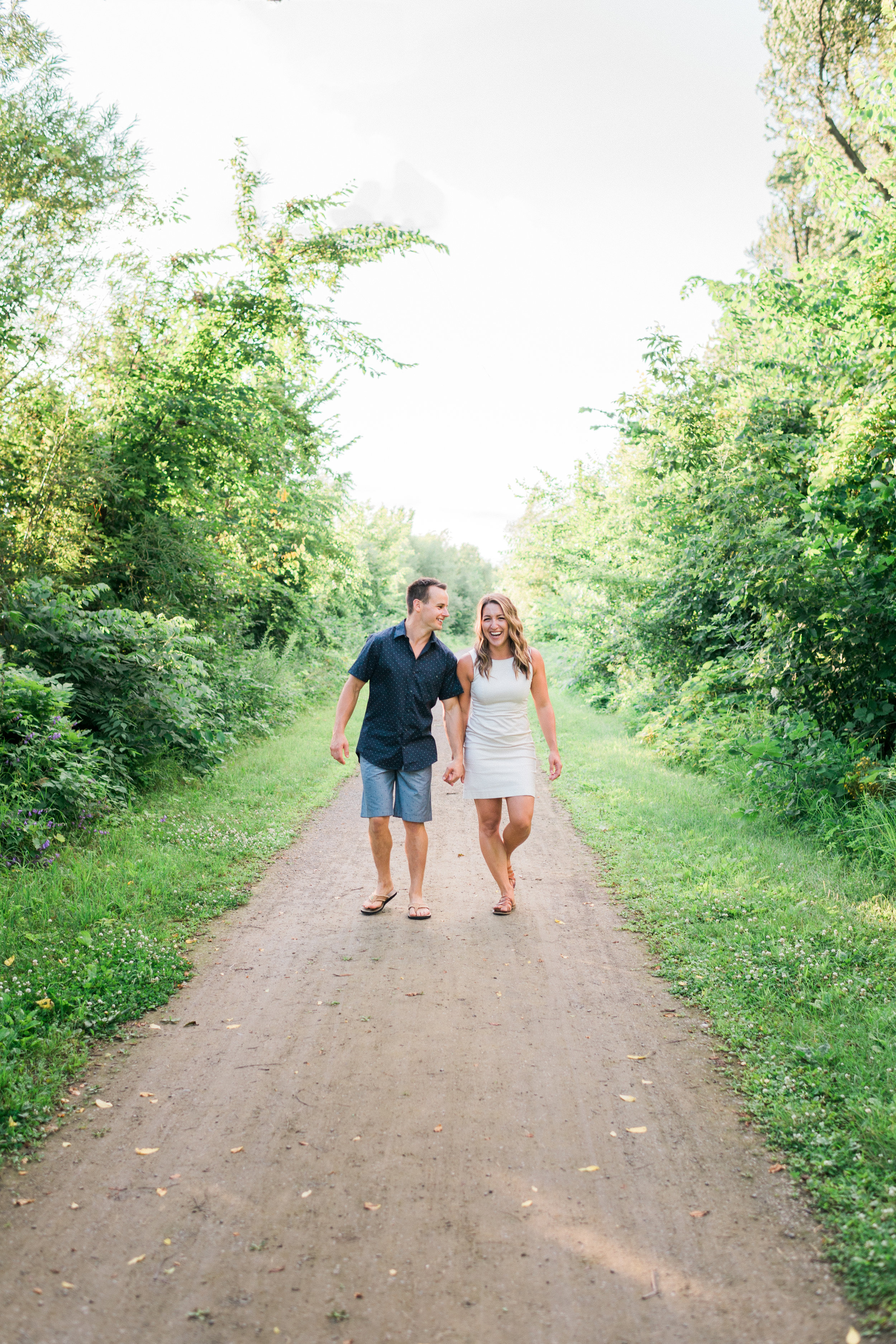 Engaged couple laughs and hold hands as they walk down a path.