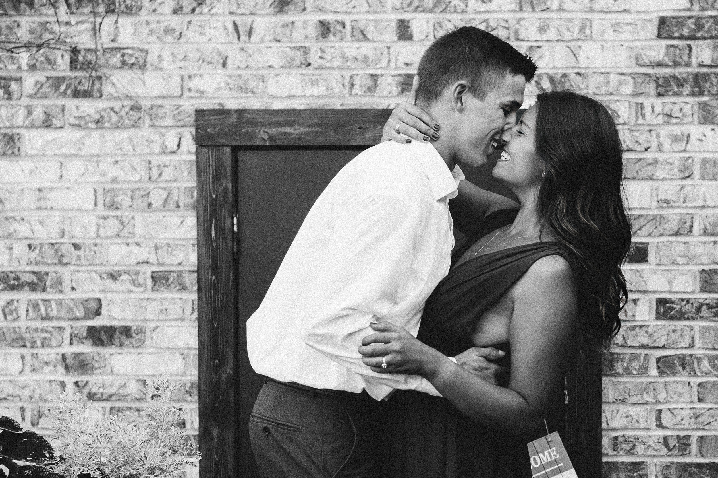 Man dips his fiancé back as he rubs noses with her in front of a brick wall.