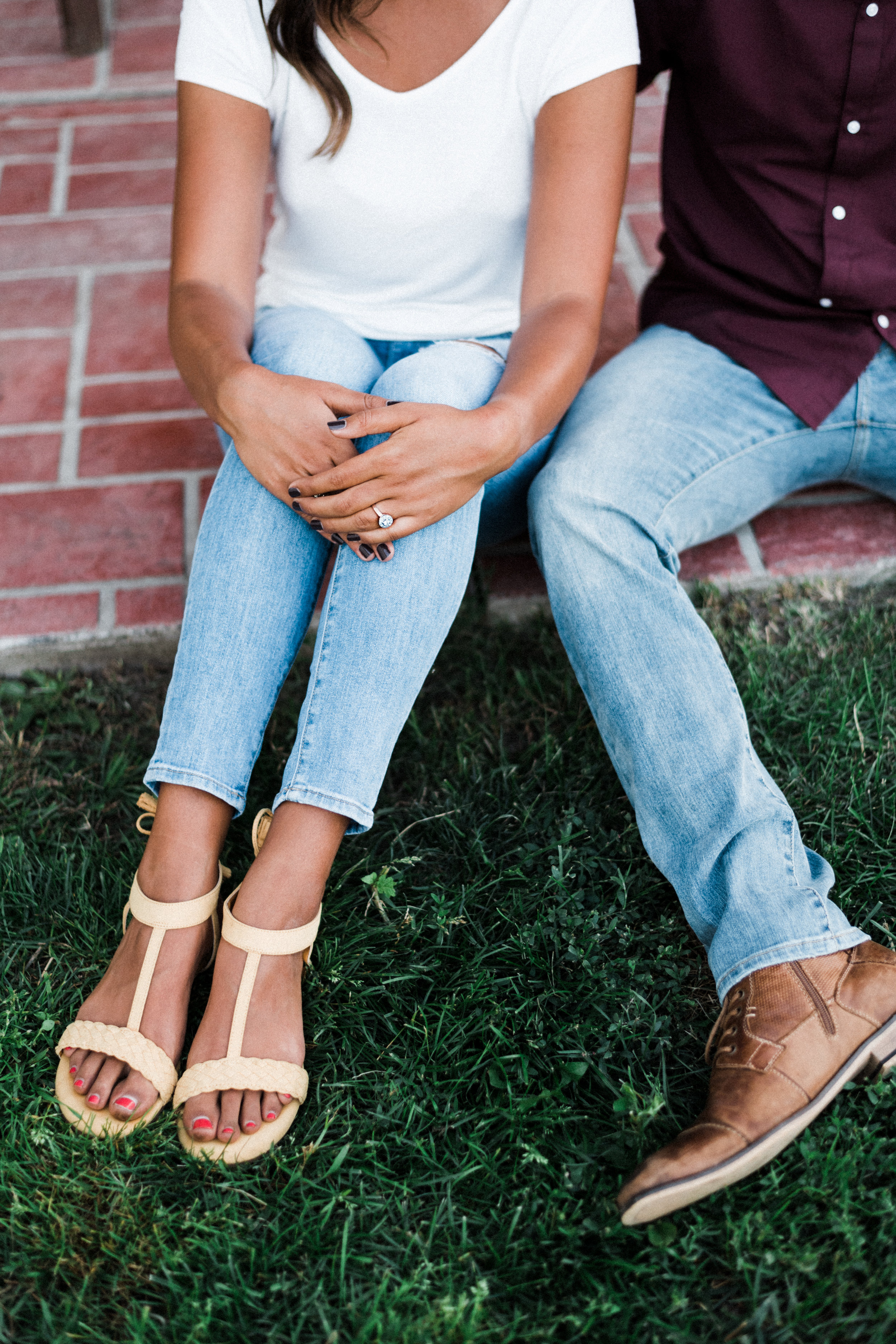 Woman wearing jeans and yellow sandals shows off her engagement ring.