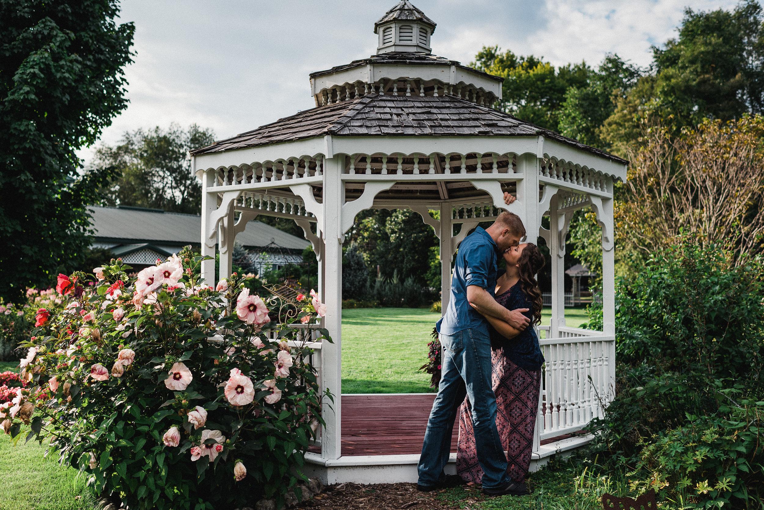 Man leans against a garden gazebo as he kisses his fiance.