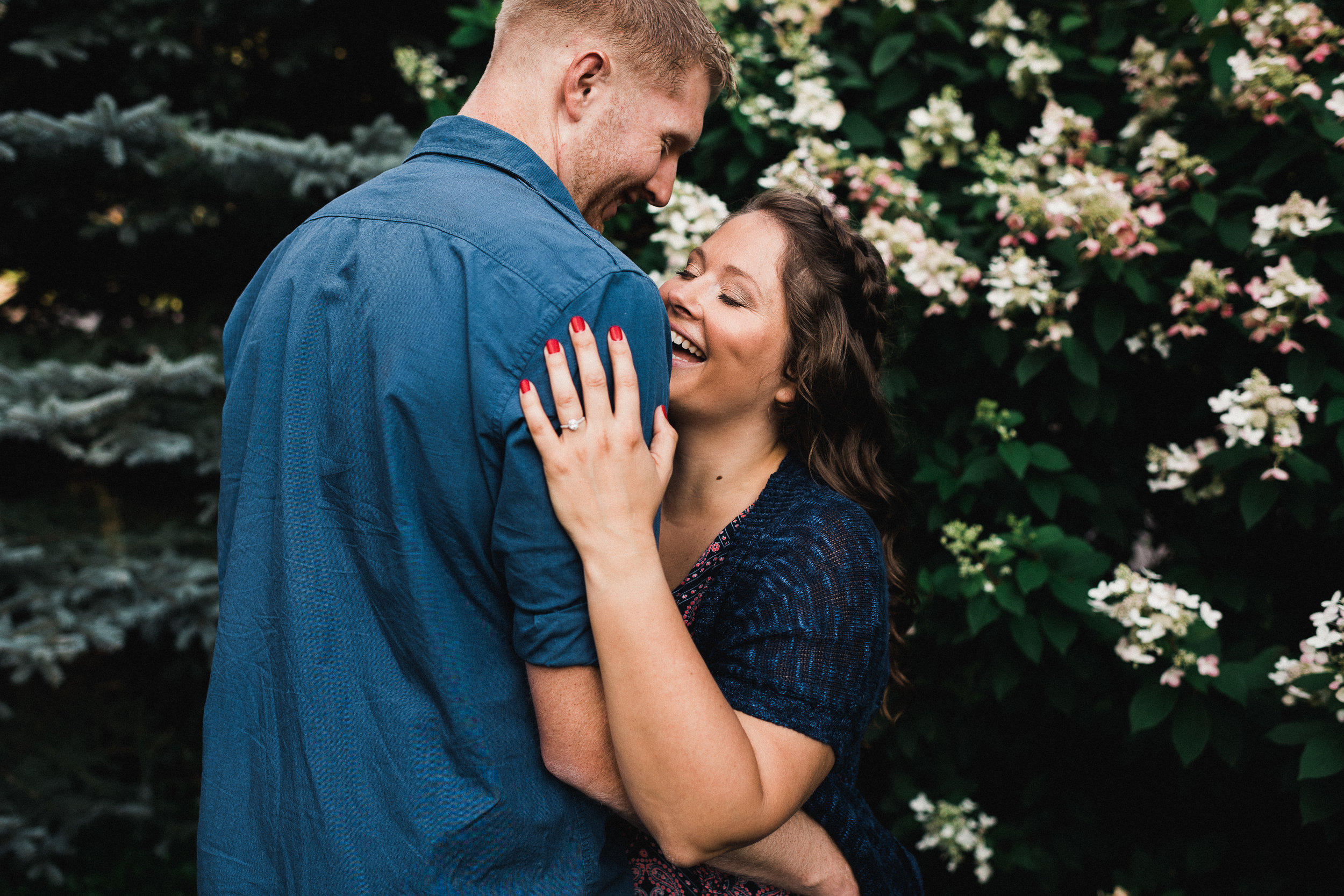 Woman laughs with her eyes closed as she holds on to her fiance.