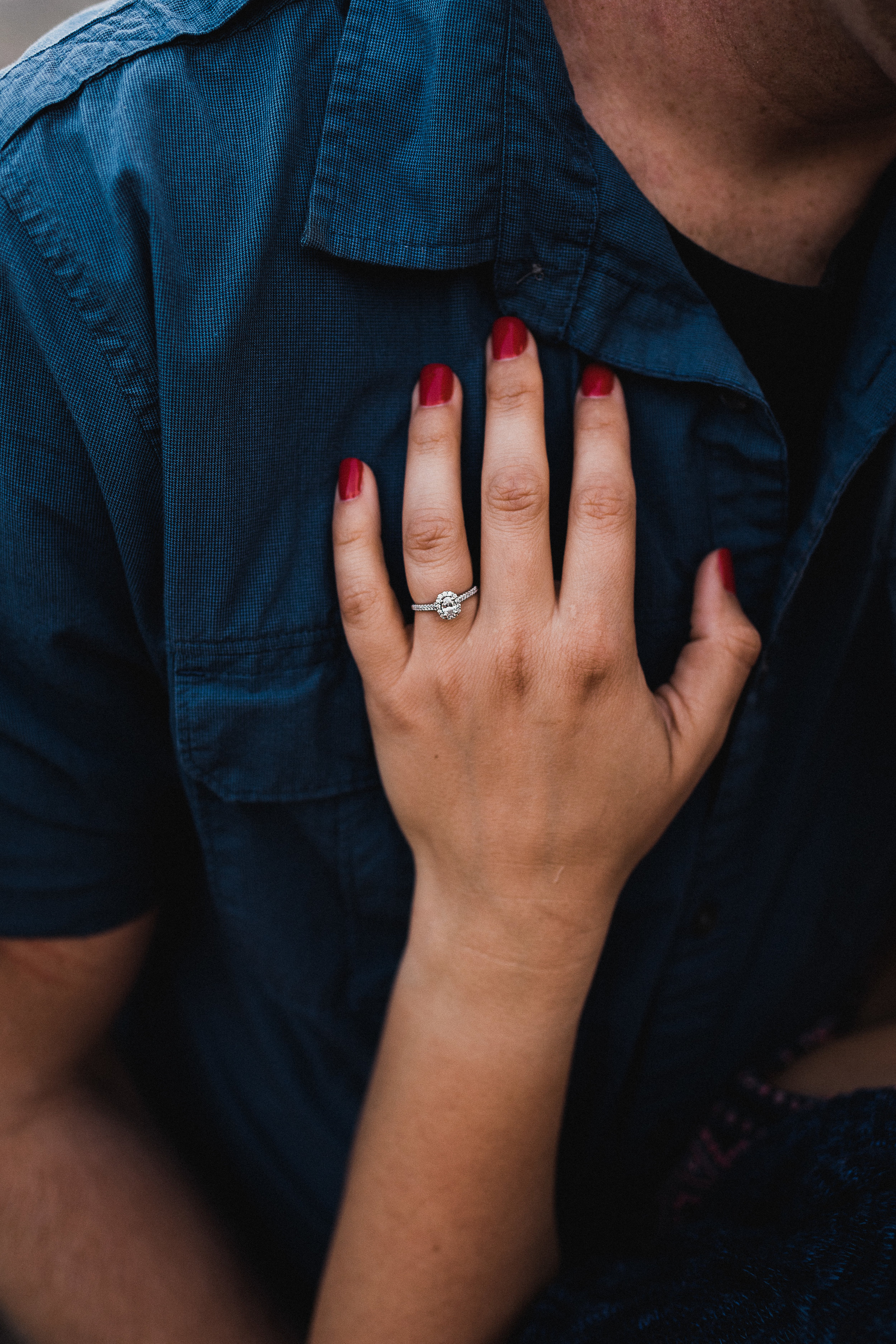 Woman places her hand on her fiance's chest and shows her engagement ring.