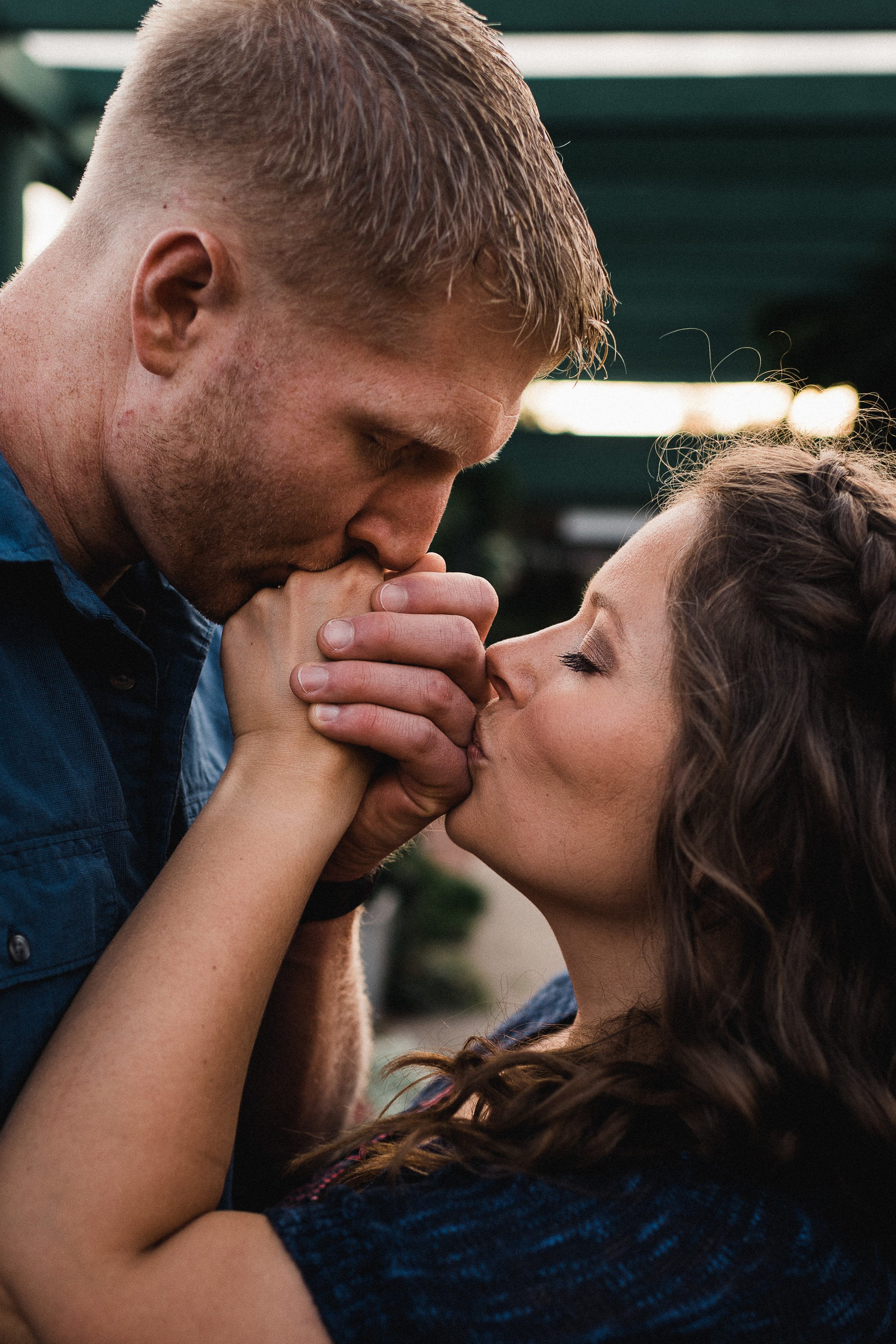Engaged couple holds hands and kisses each other's hands with eyes closed.