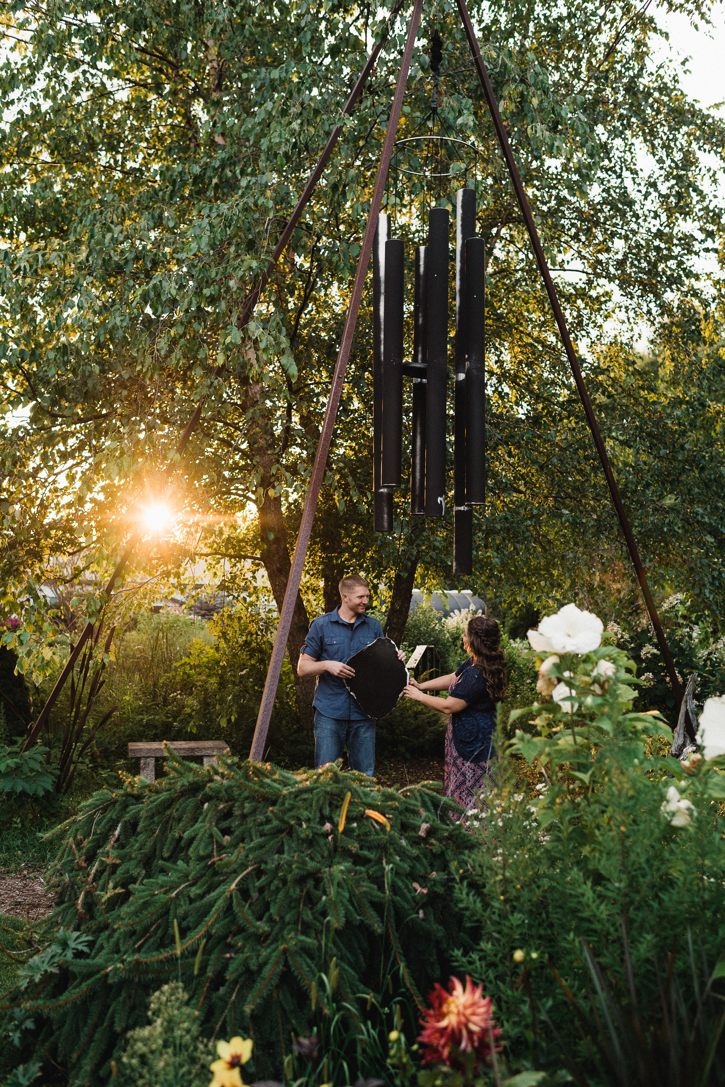 Engaged couple work together to make a gigantic garden wind chime make noise.