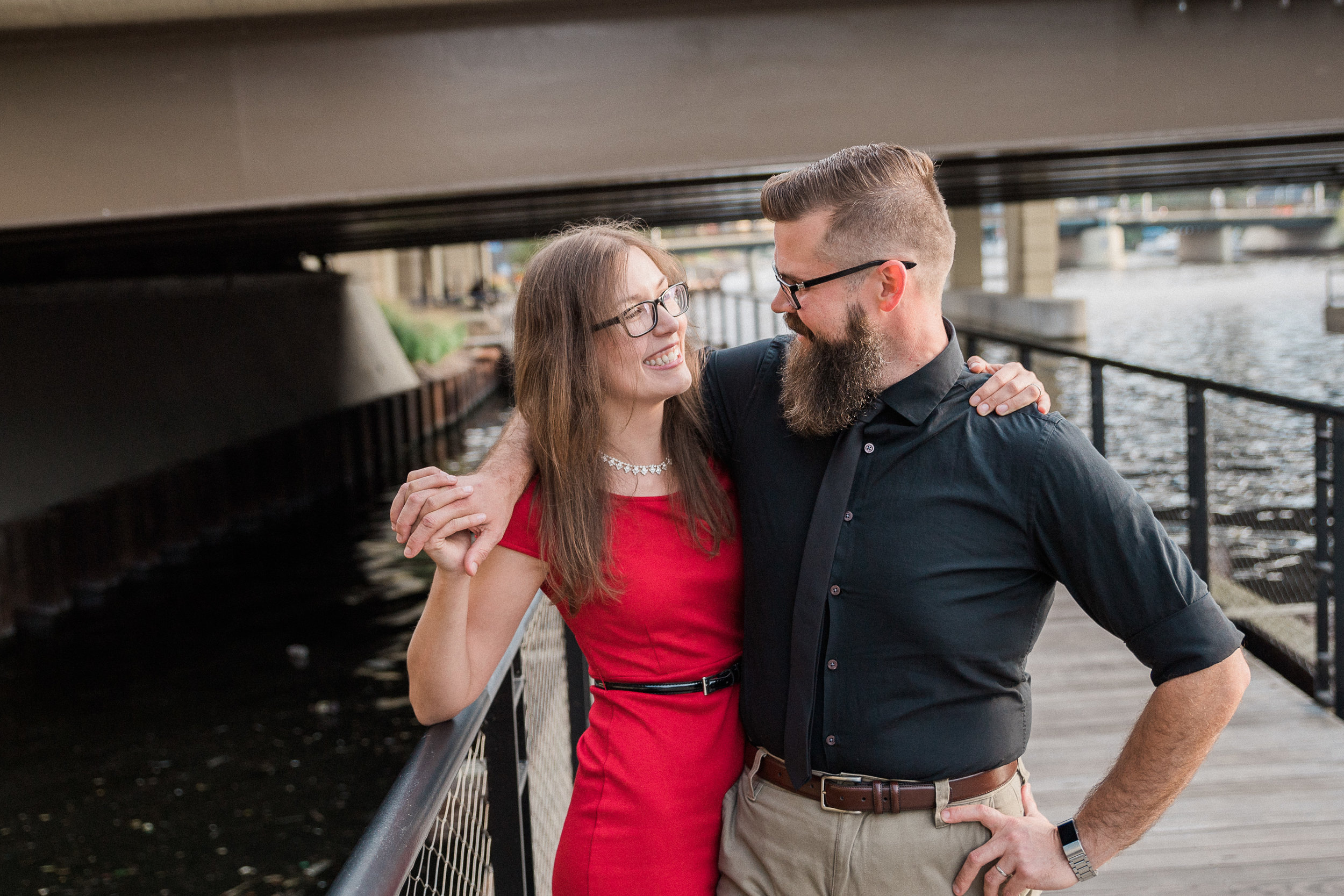 Engaged couple wraps arms around each other's shoulder at the Milwaukee Riverwalk.