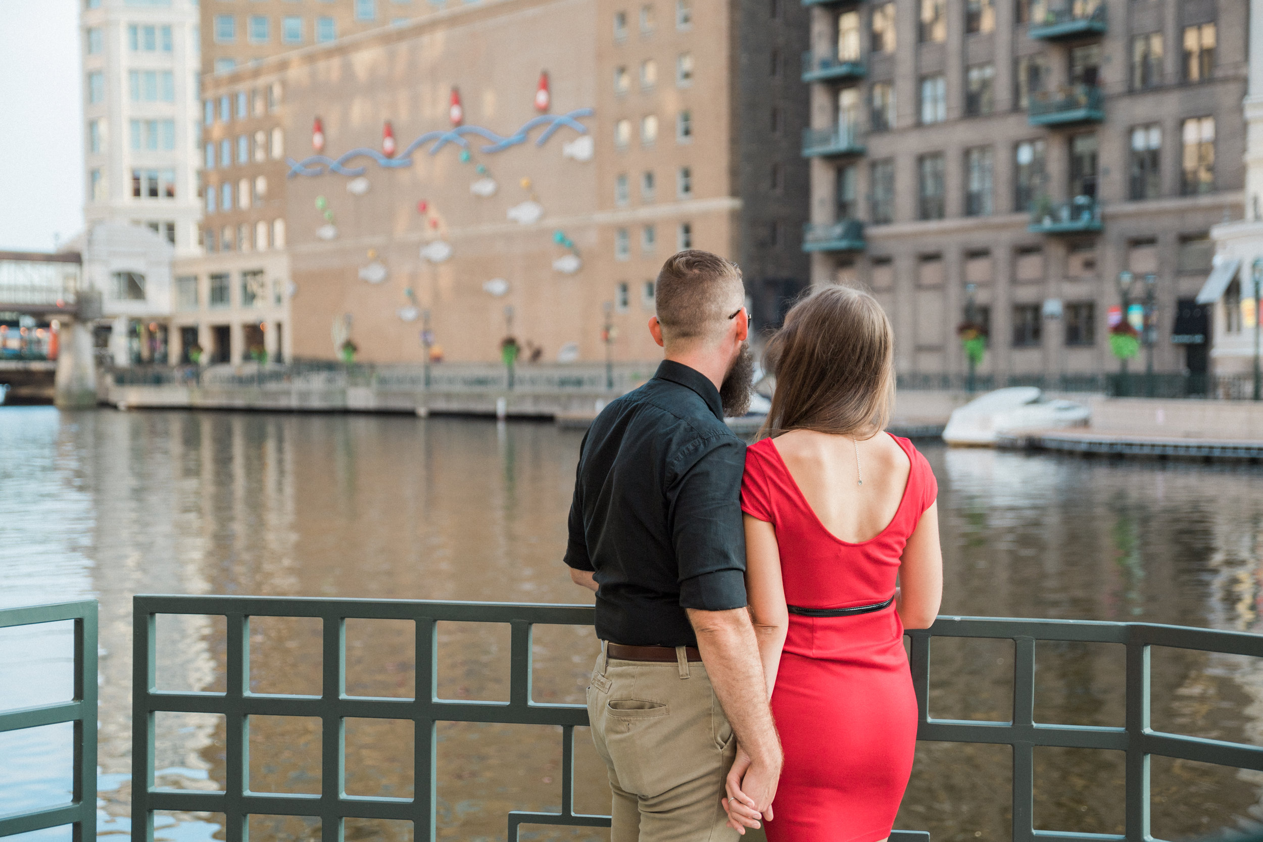 Engaged couple holds hands and looks out at the Milwaukee River from the Milwaukee Riverwalk.