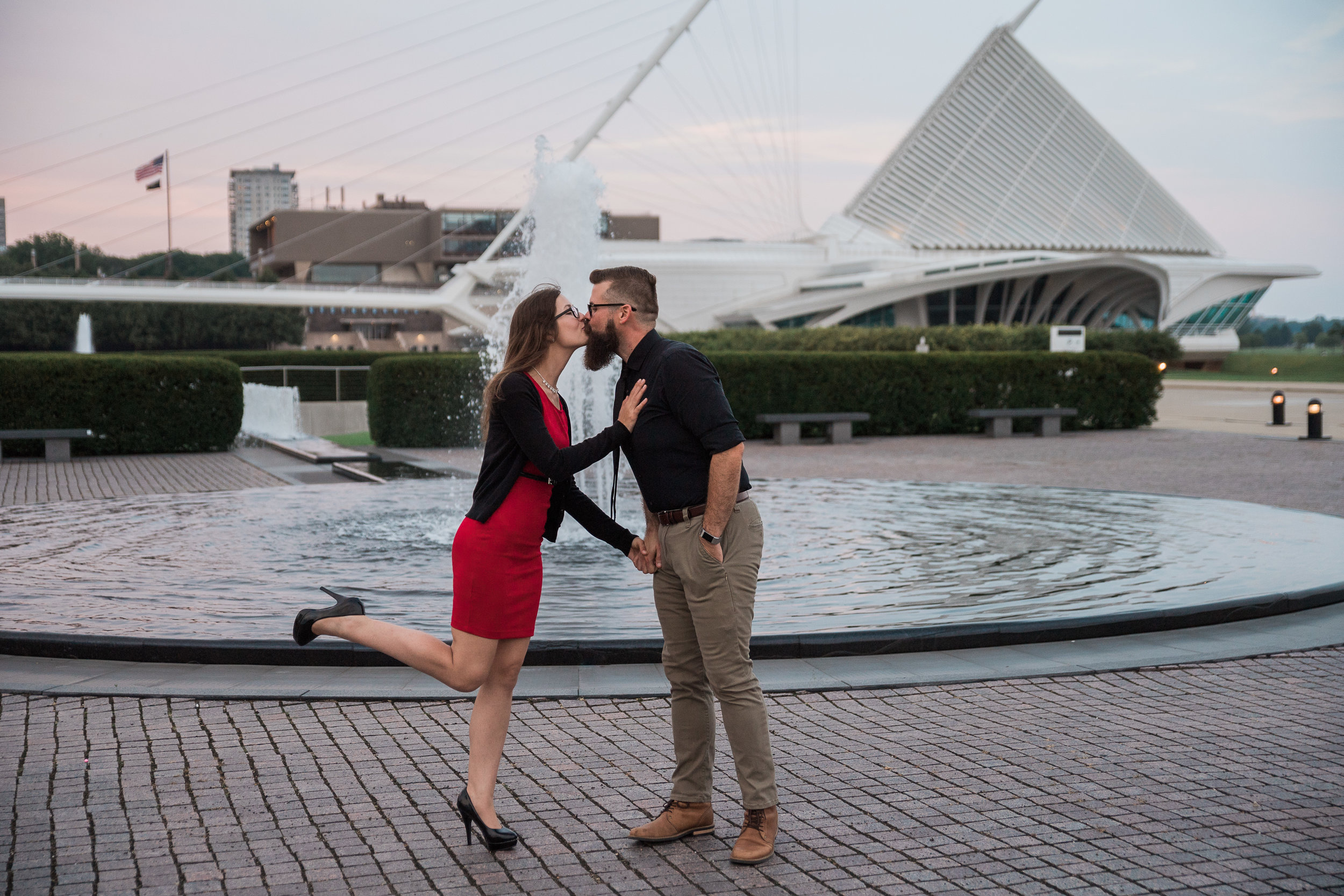 Engaged couple kisses in front of the fountain at Milwaukee Art Museum.