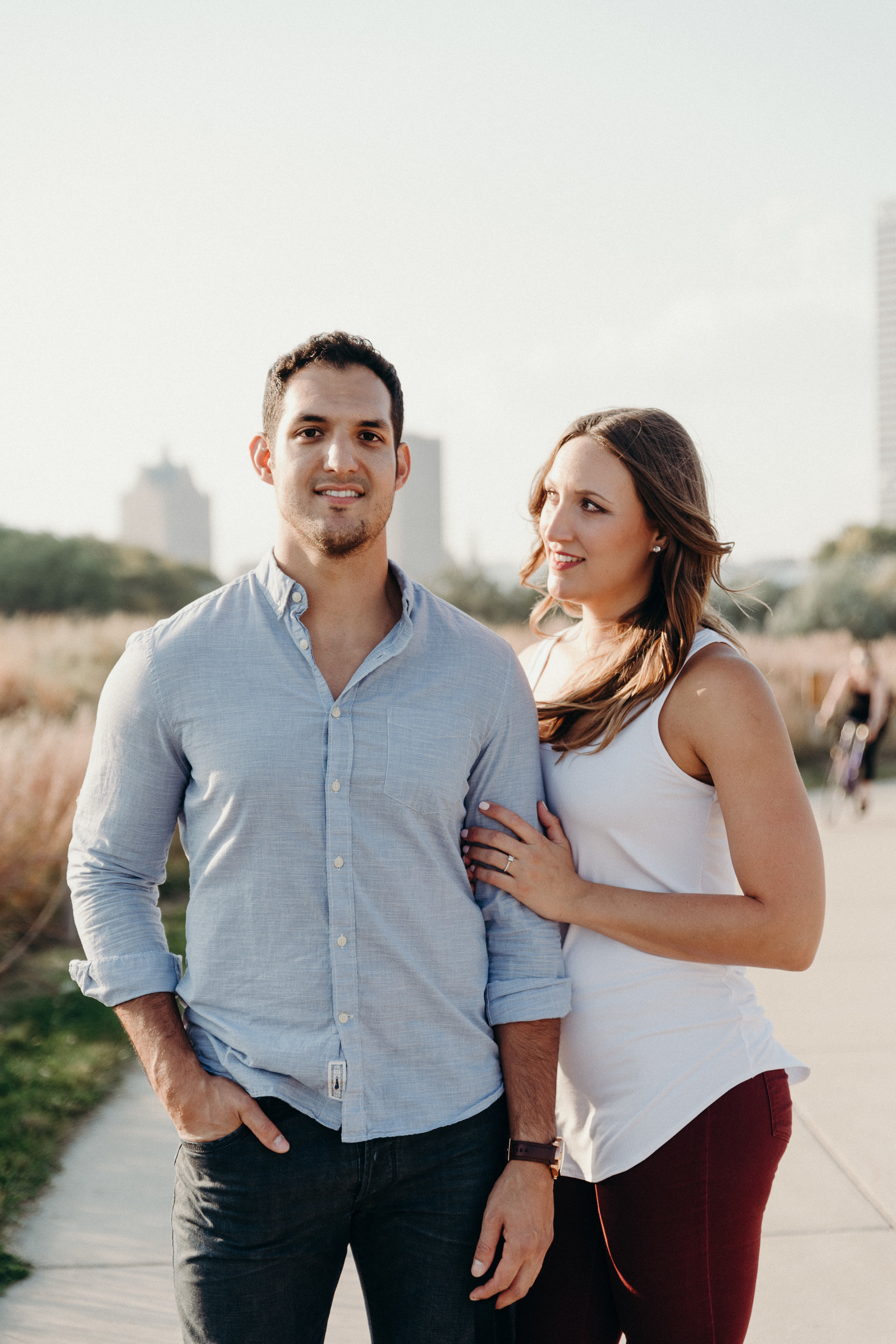 Woman looks at her fiancé while holding his arm.