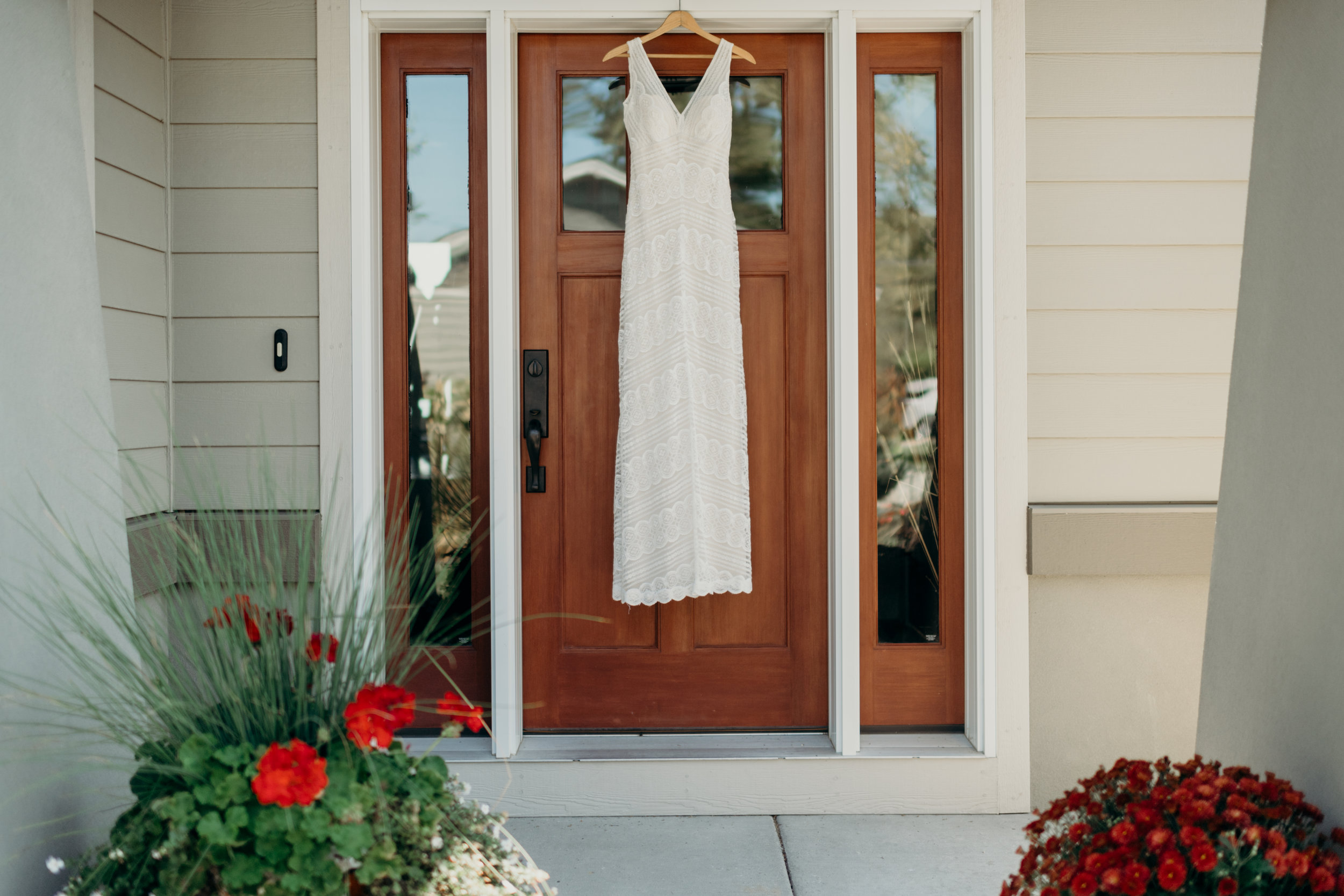 Lace bridal gown hanging on a front door.