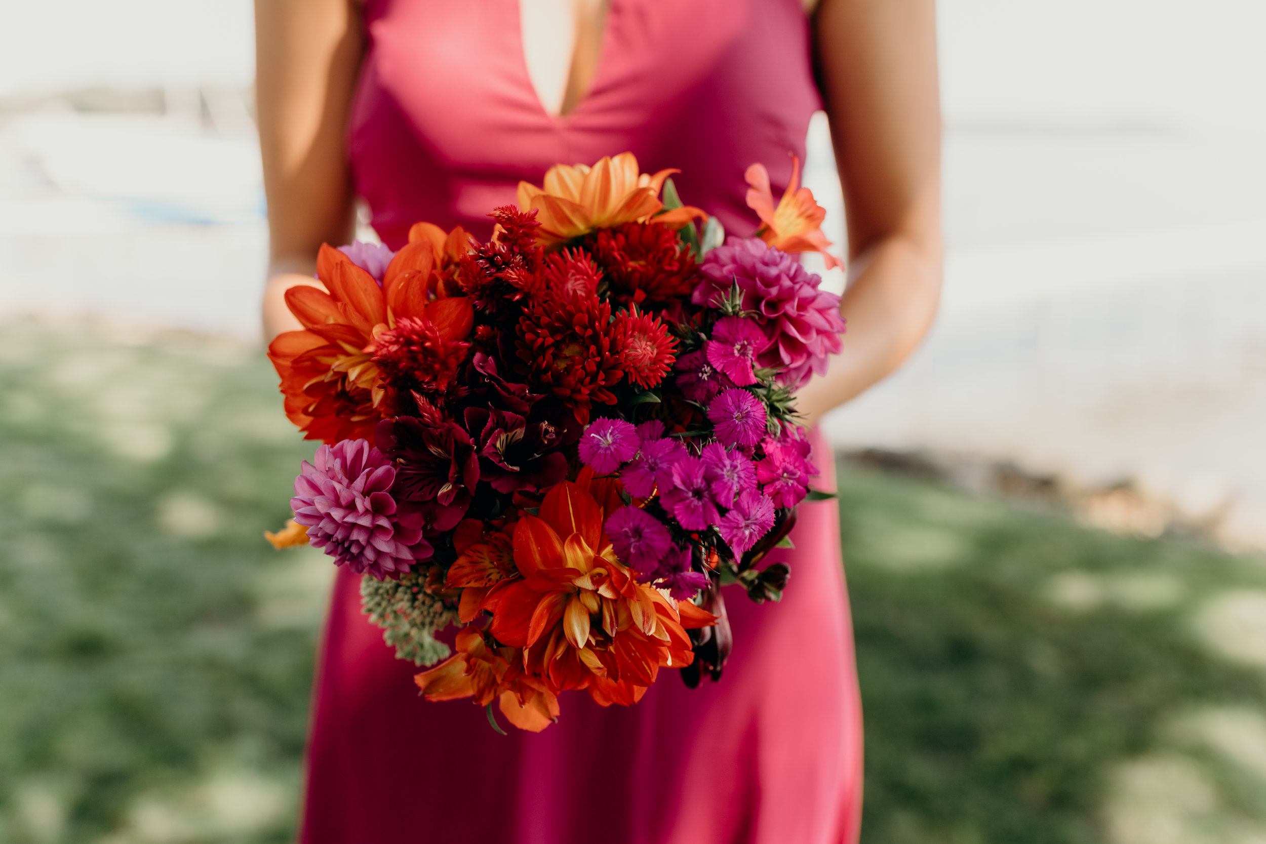 Bridesmaid's red, purple, and orange bouquet.