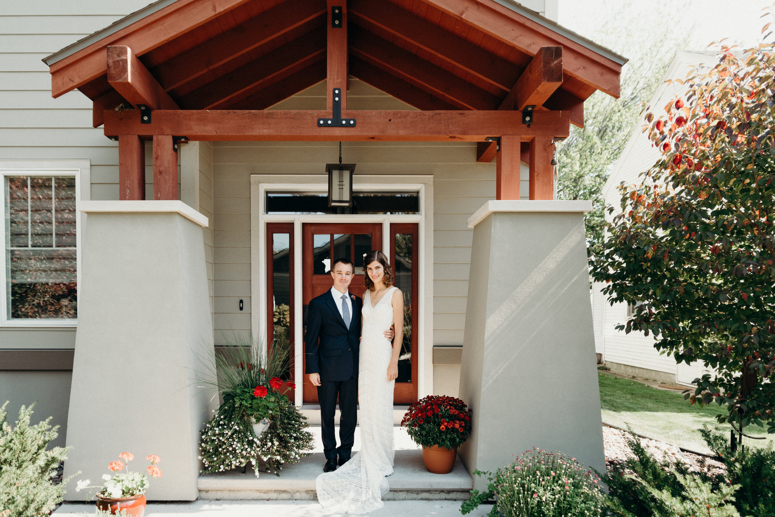 Bride and groom pose for a portrait on the front porch.
