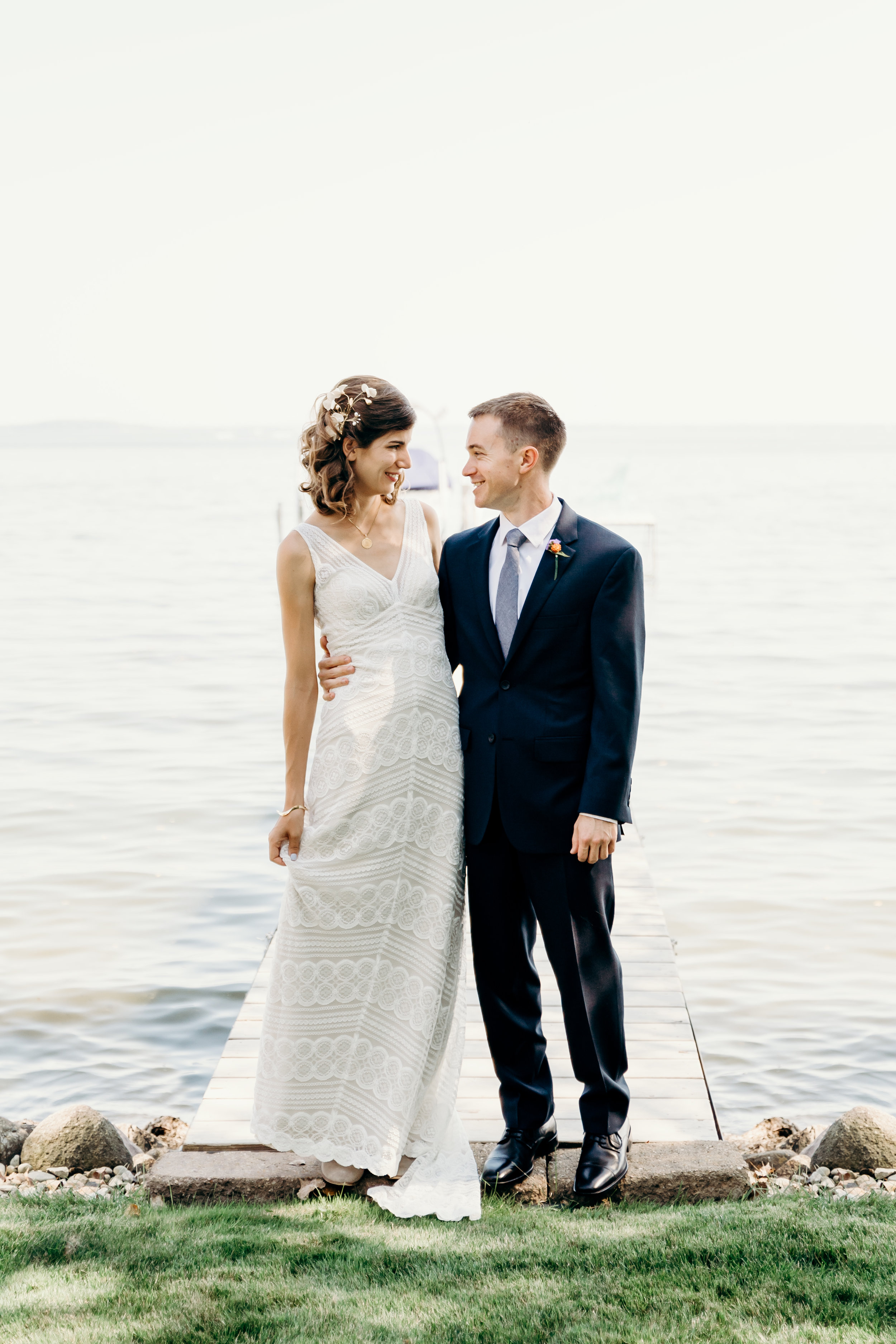 Bride and groom smile at each other at the edge of a dock.