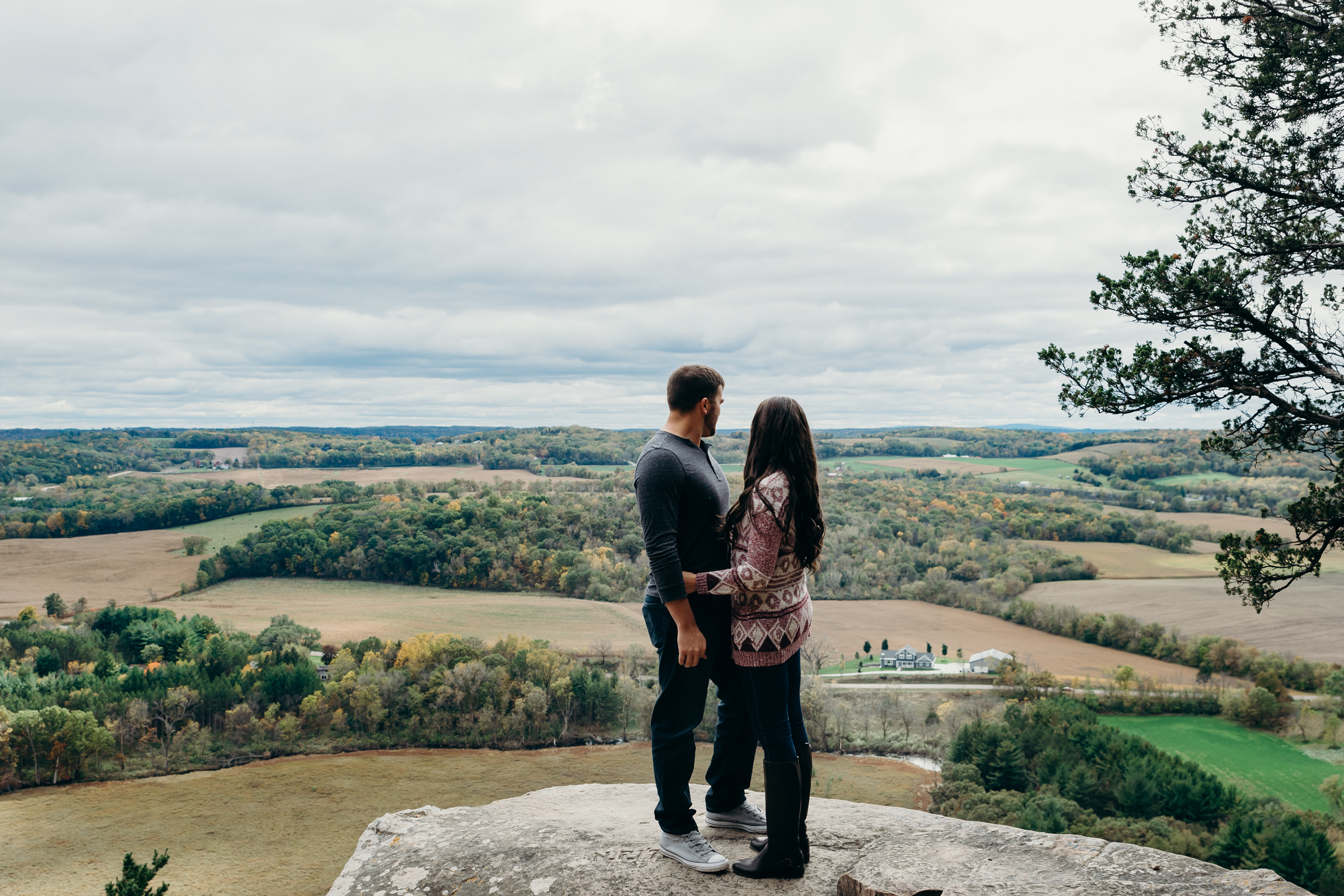 Engaged couple stands on top of a rock overlooking Lodi, WI at Gibraltar Rock State Natural Area.