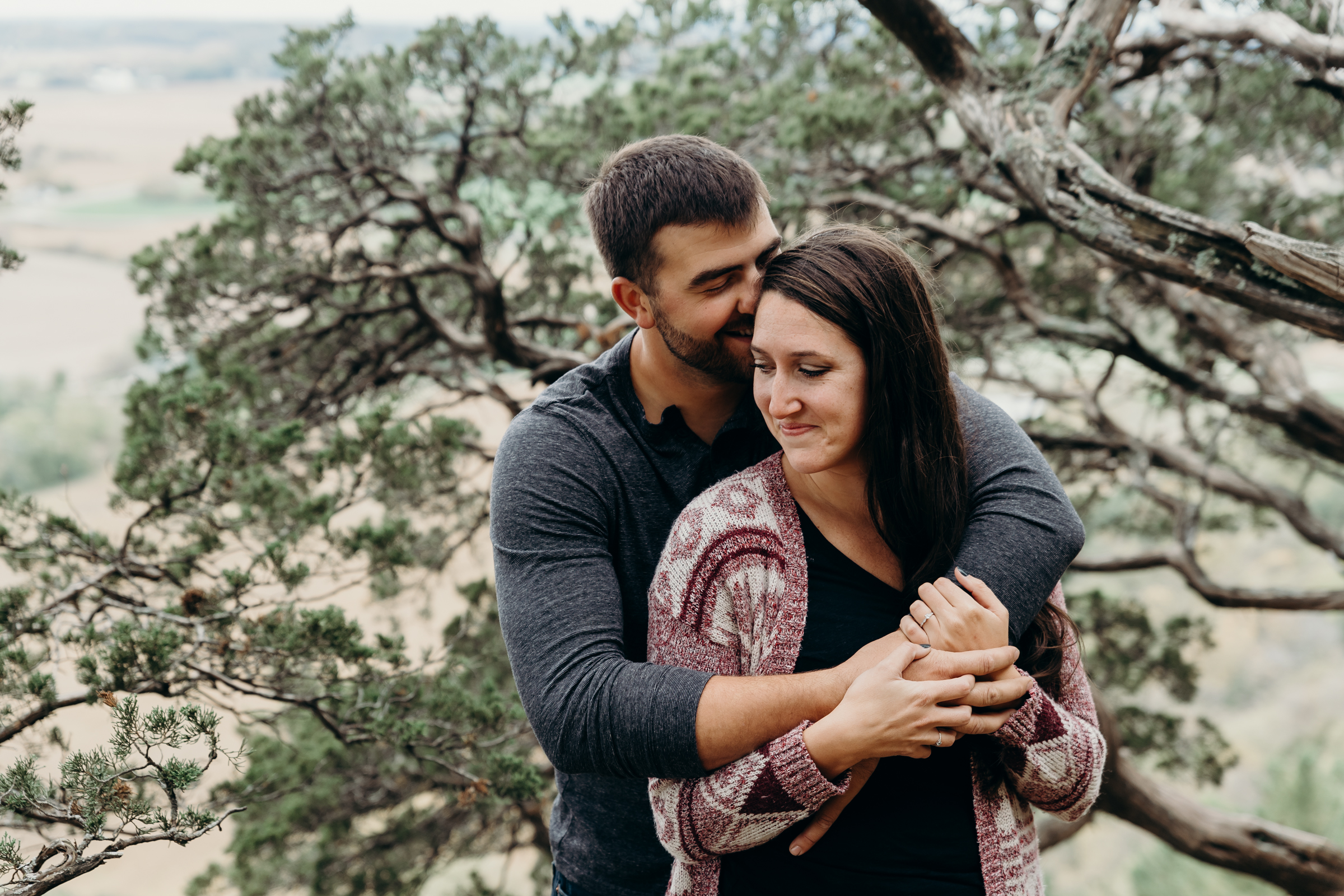 Man wraps his arms around his fiancé and giggles into her hair.