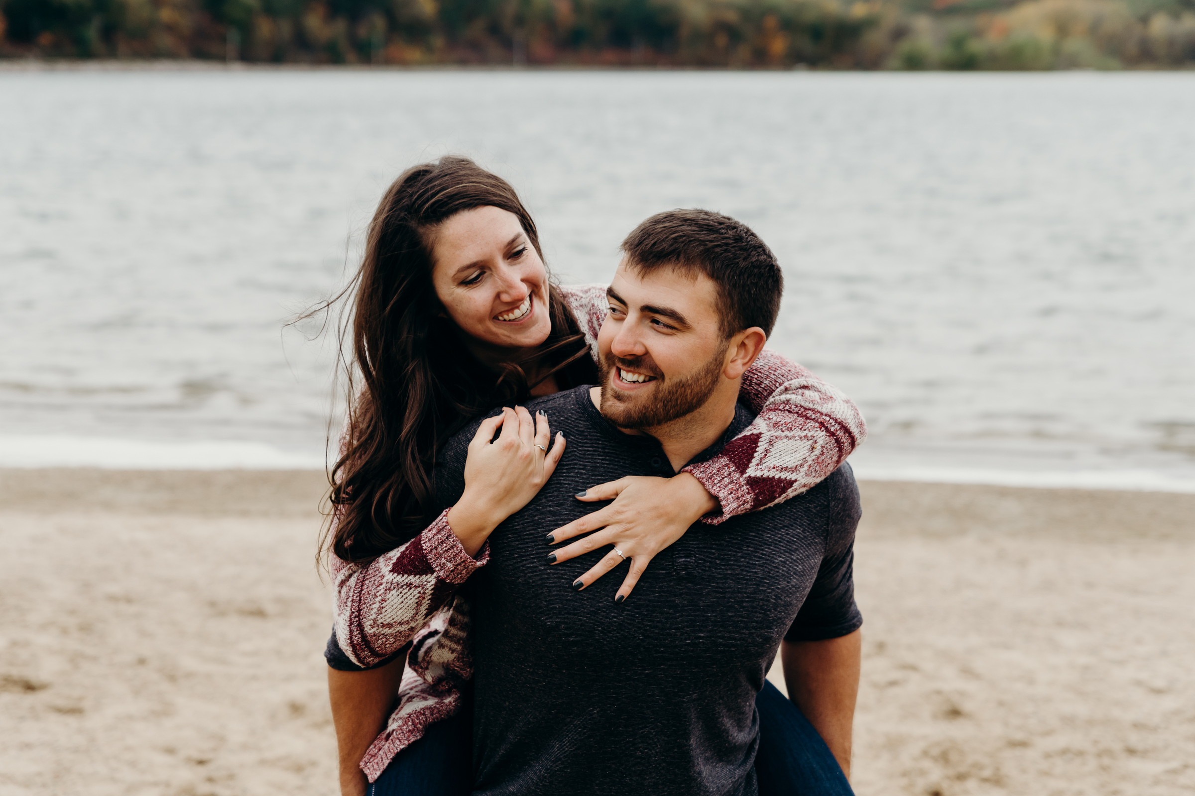 Engaged couple smile at each other while the man gives his fiancé a piggy back ride.