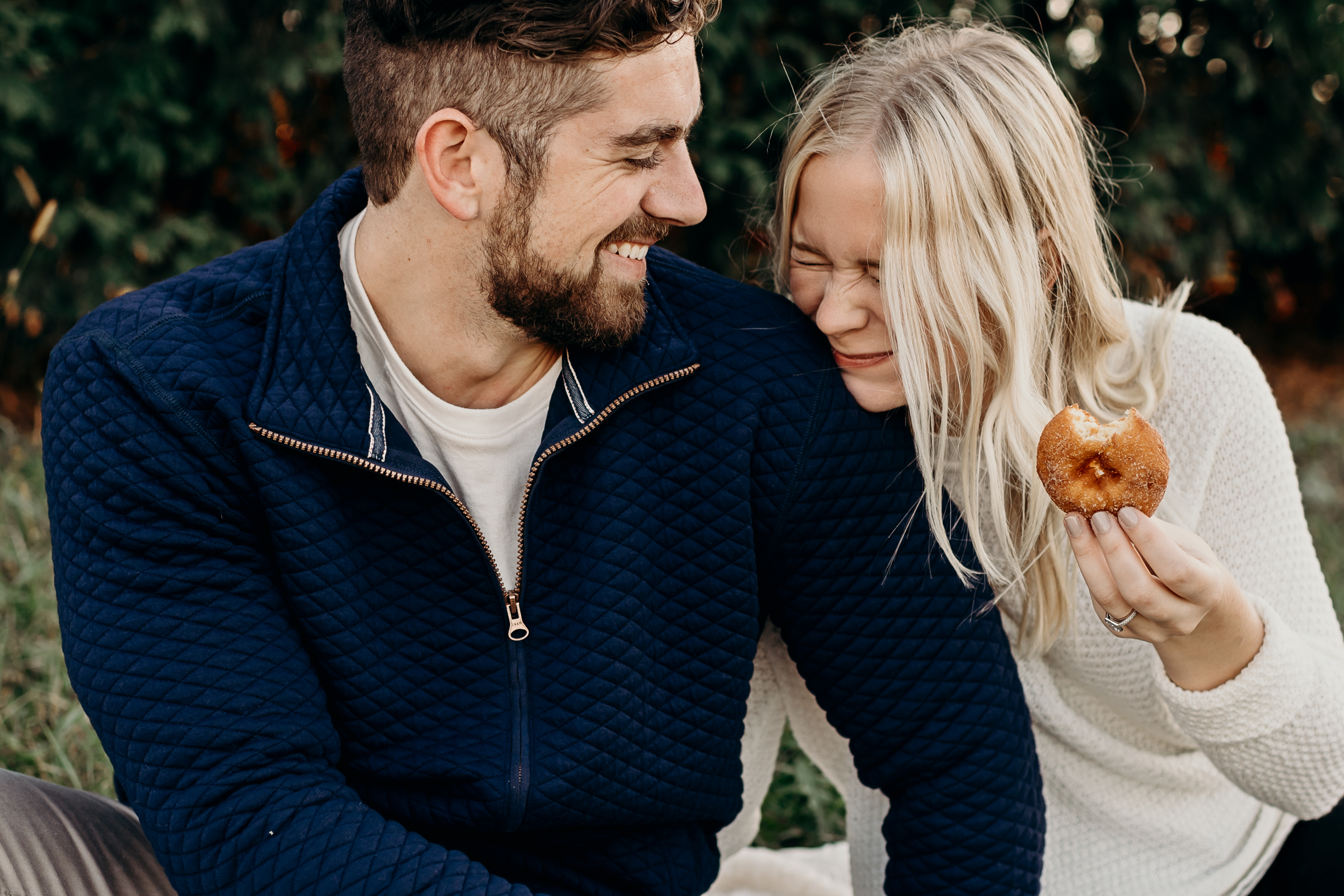 Woman laughs as she eats a donut with her fiancé.