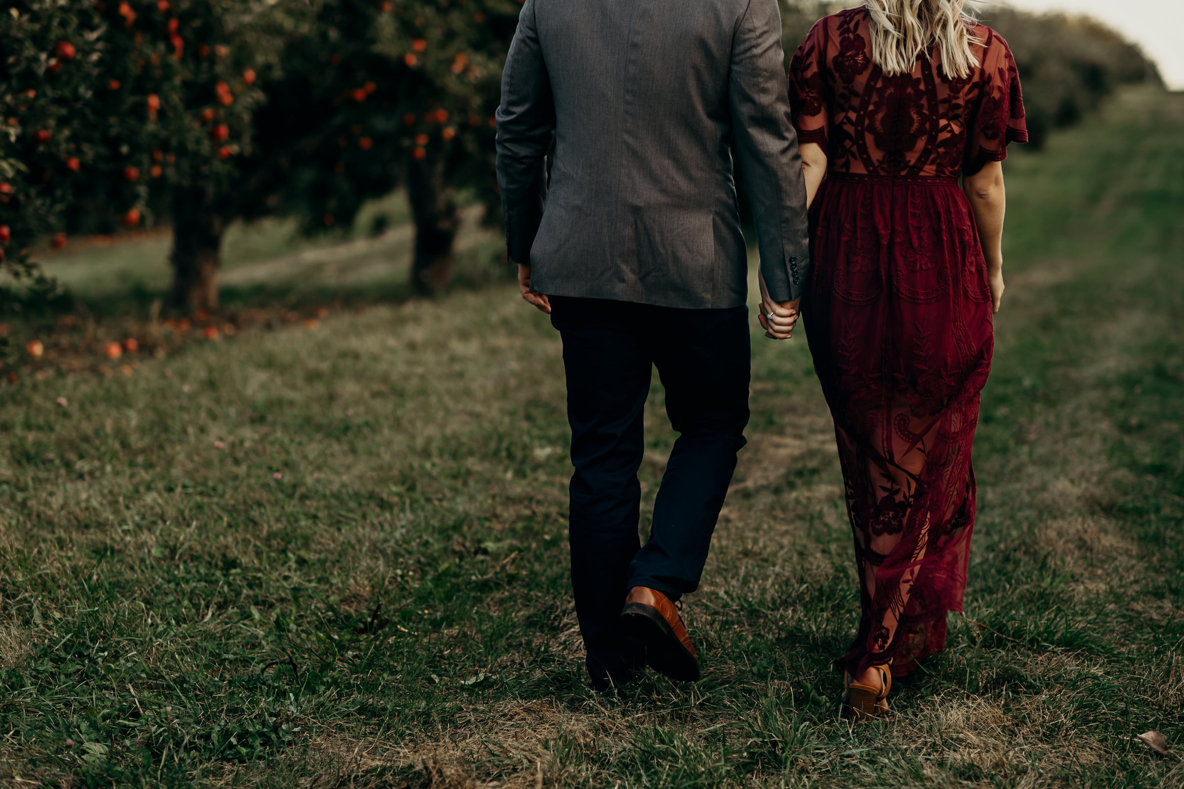 Engaged couple holds hands as they walk through an apple orchard.
