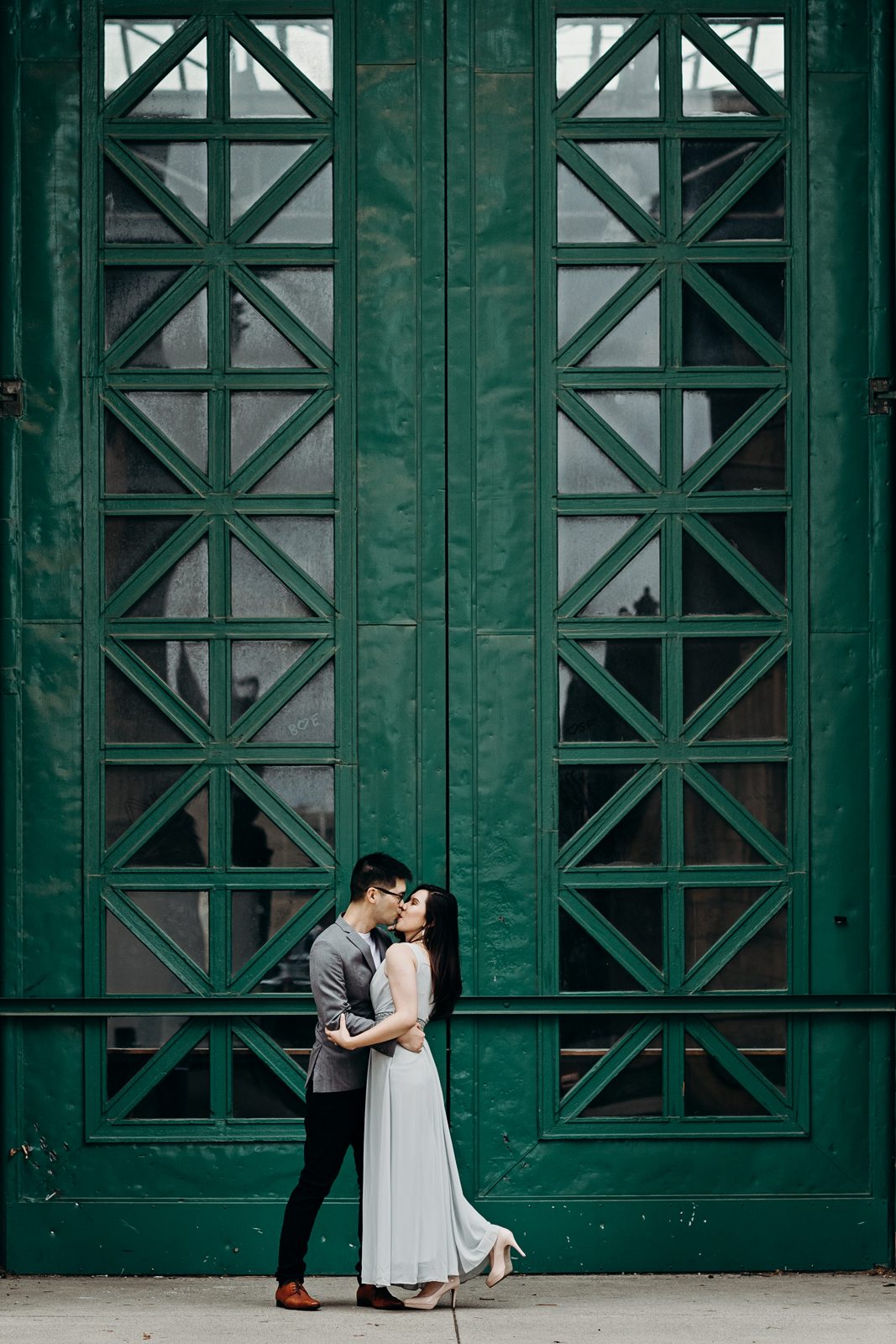 Engaged couple kisses in front of a tall green door at Palace of Fine Arts. Theatre in San Francisco, CA.