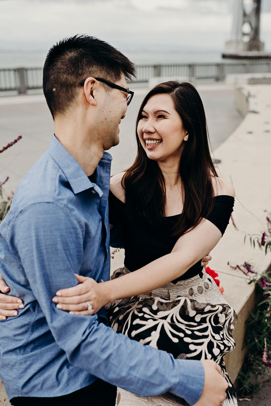 Engaged couple sits by the San Francisco–Oakland Bay Bridge and smiles at each other.