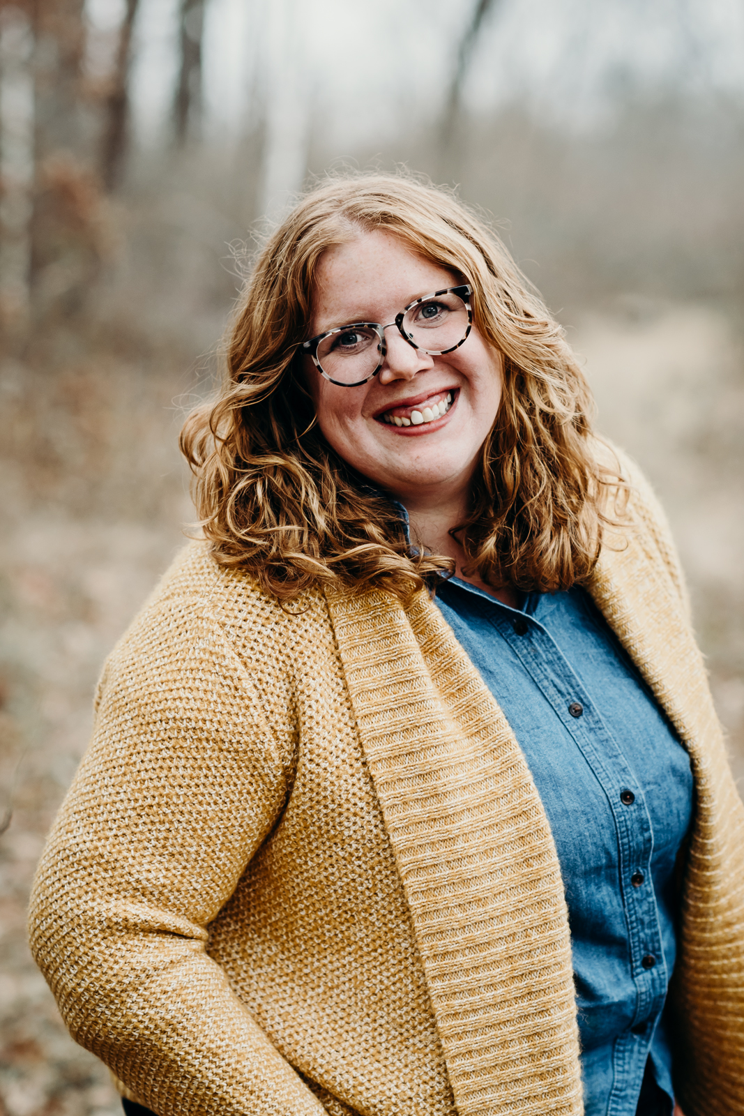 Woman in a mustard colored cardigan and denim shirt smiling.