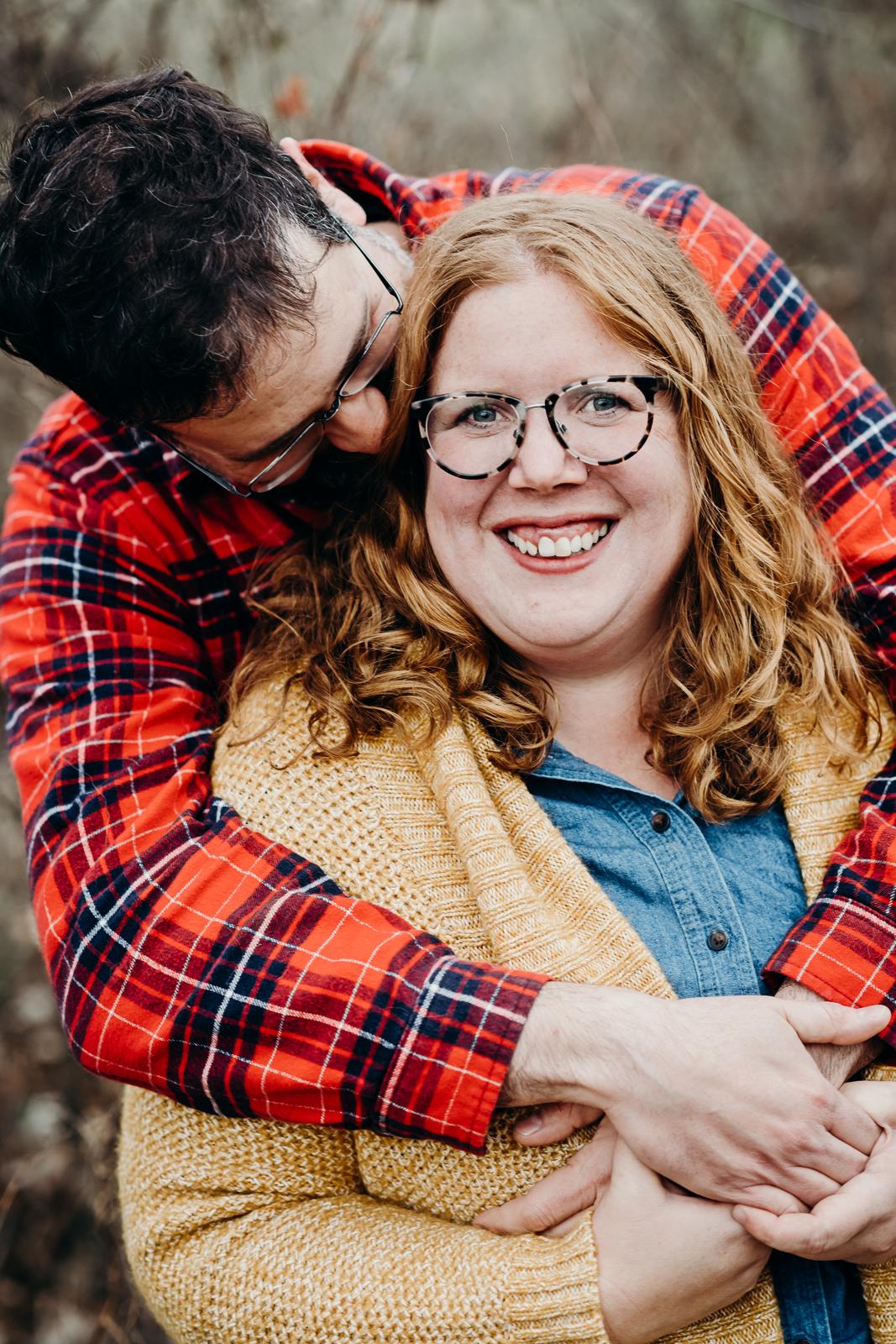 Man gives his fiancé a bear hug from behind.