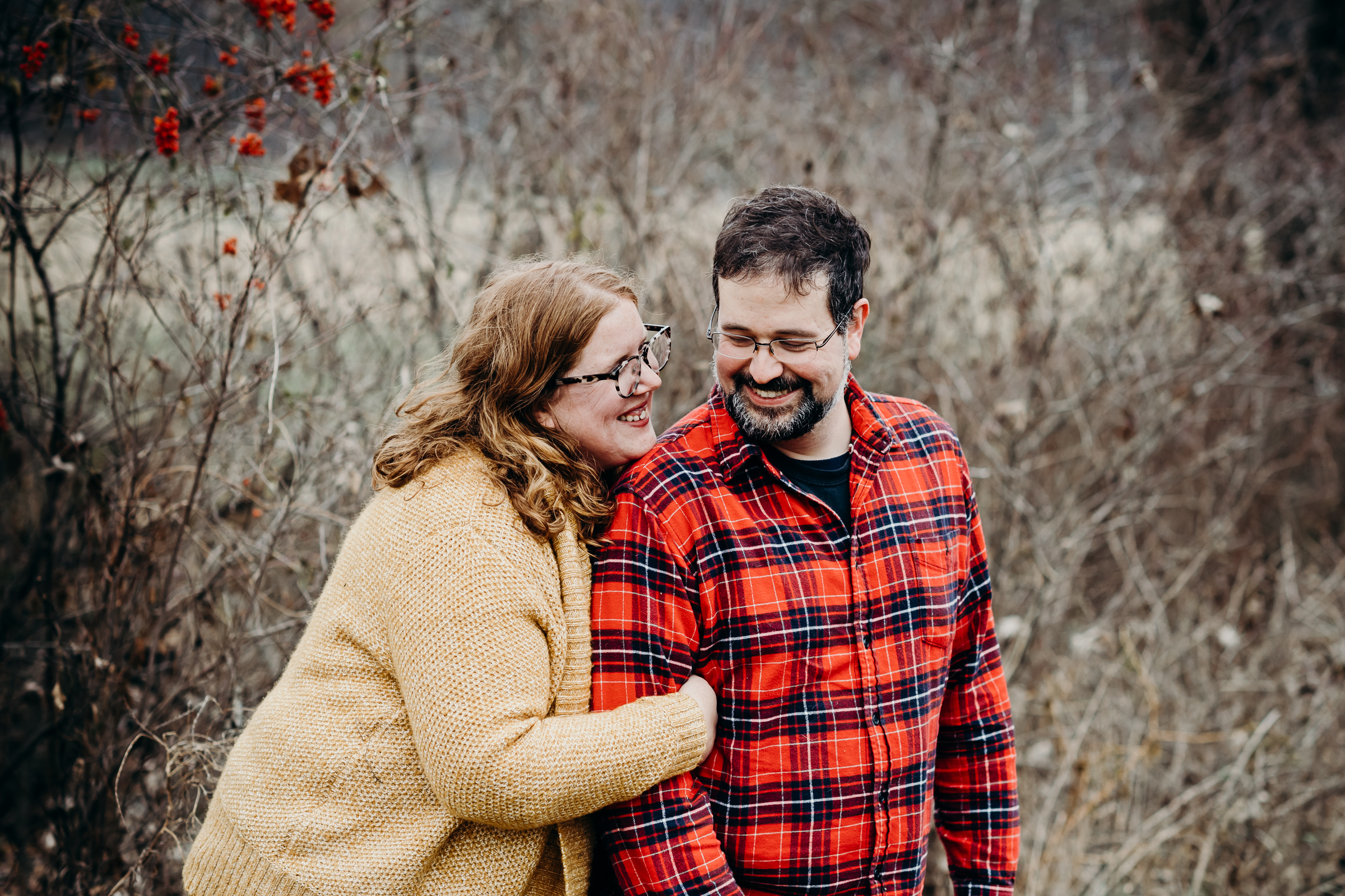 Engaged couple laughing with each other in the woods.