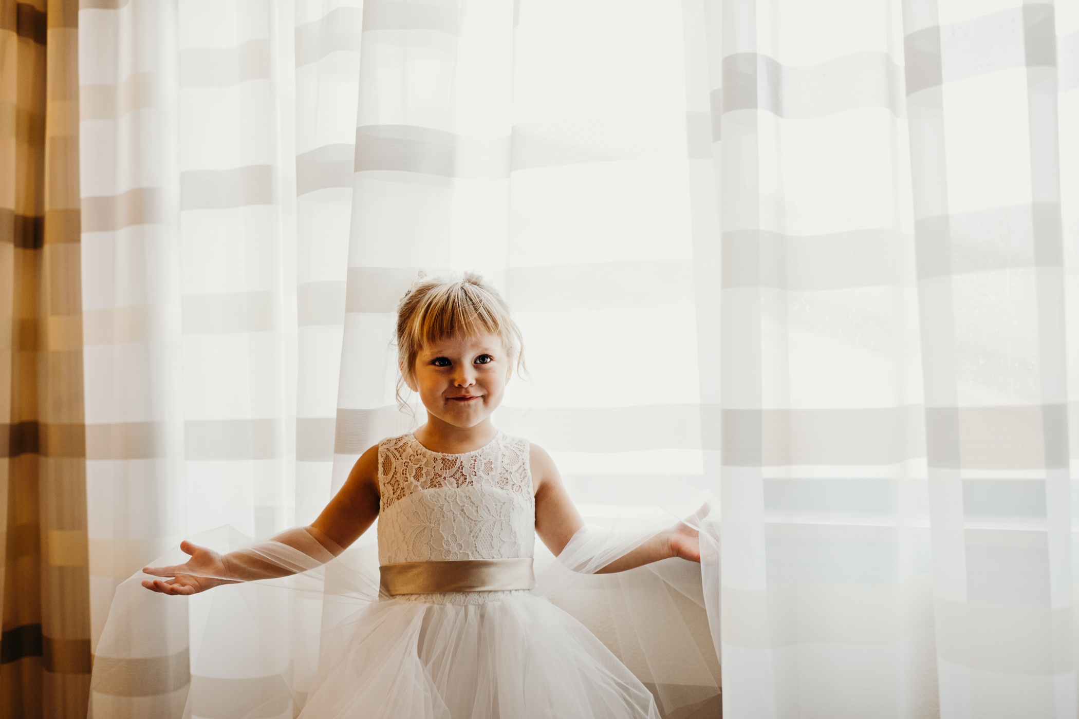 Flower girl plays with hotel room curtains