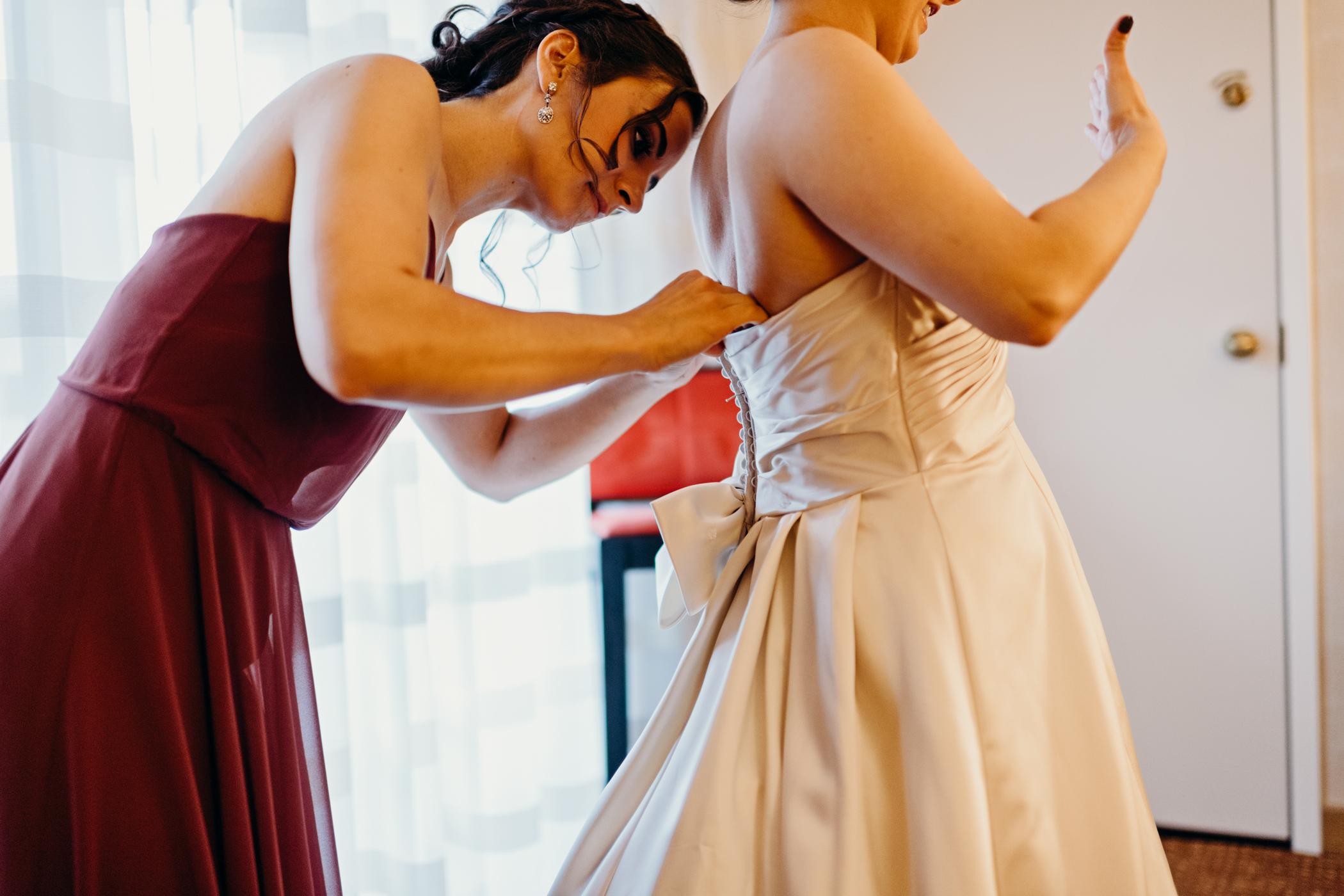 Bridesmaid fastens bride's wedding gown