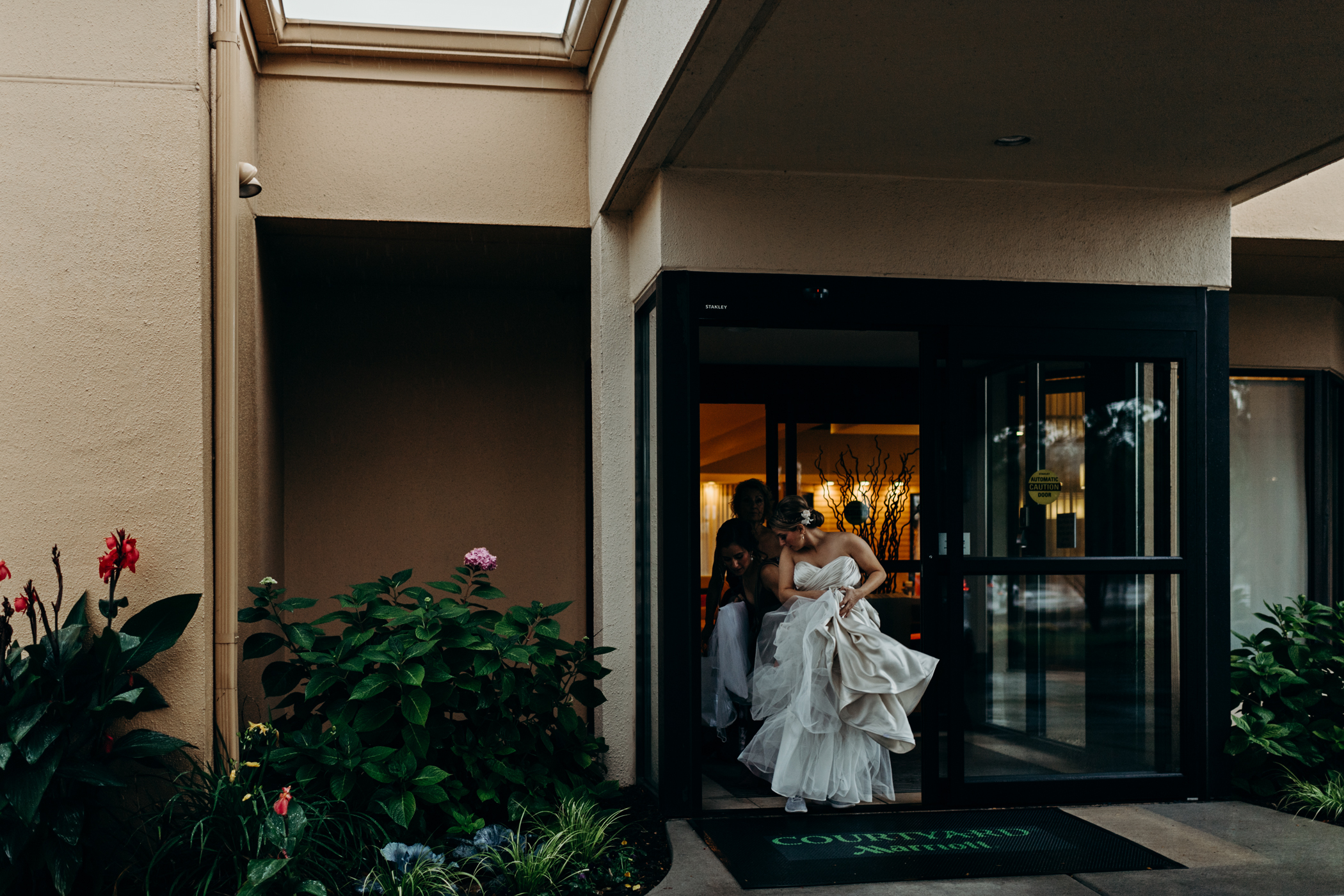 Bride holds her dress as she exits the hotel