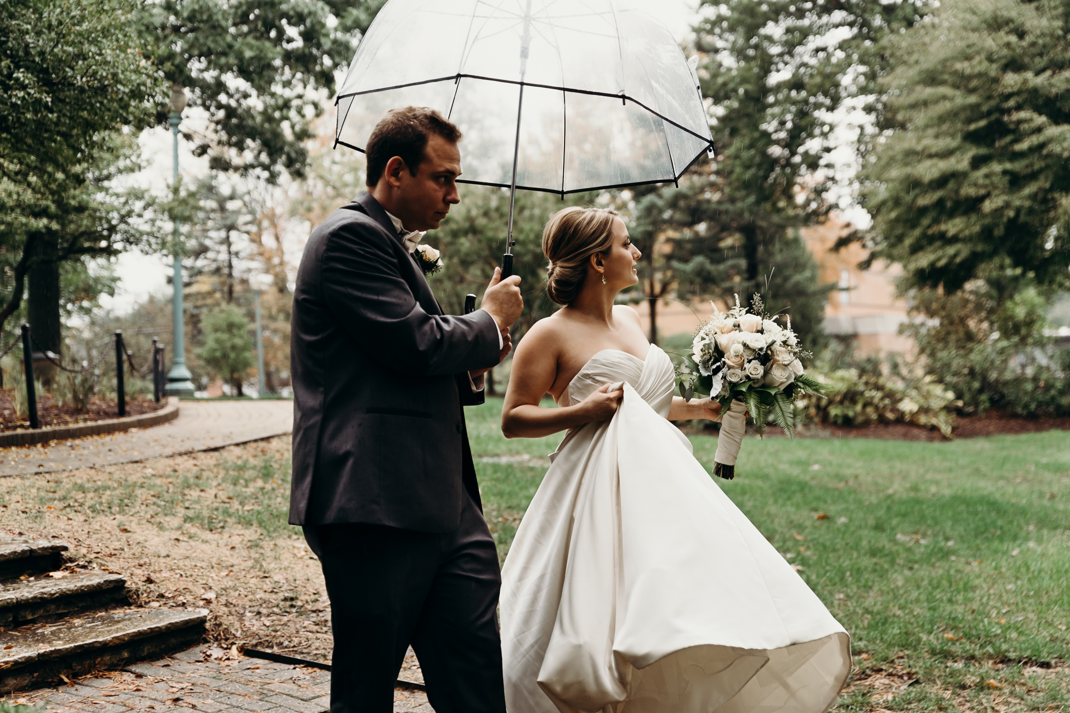 Groom holds umbrella for bride as she carries her dress