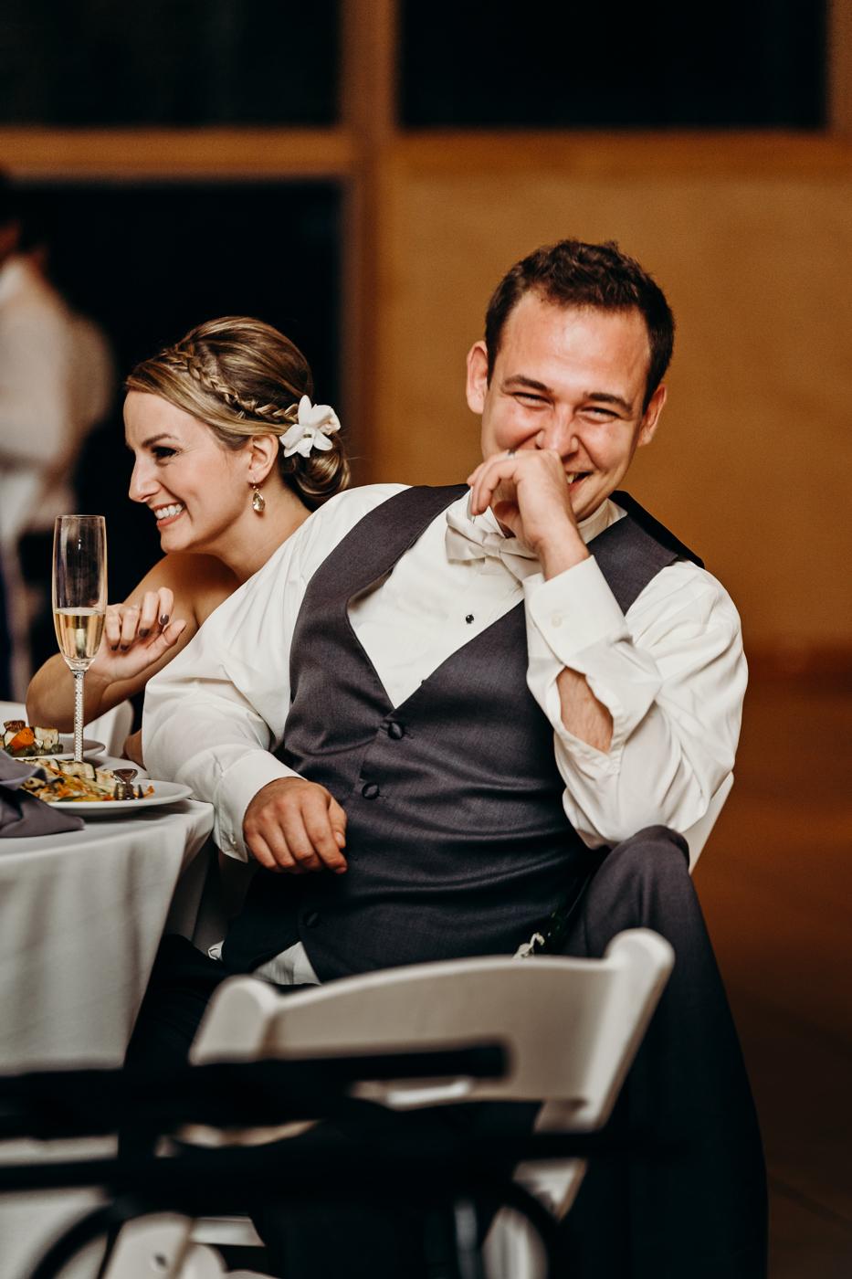Groom laughs during best man's speech