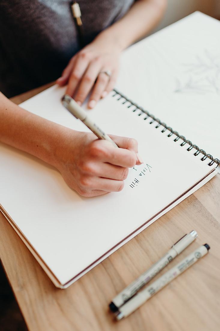 Owner of Viola Hill Studio writing in sketch book