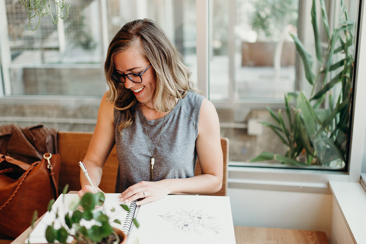 Graphic designer smiles as writing in sketch book