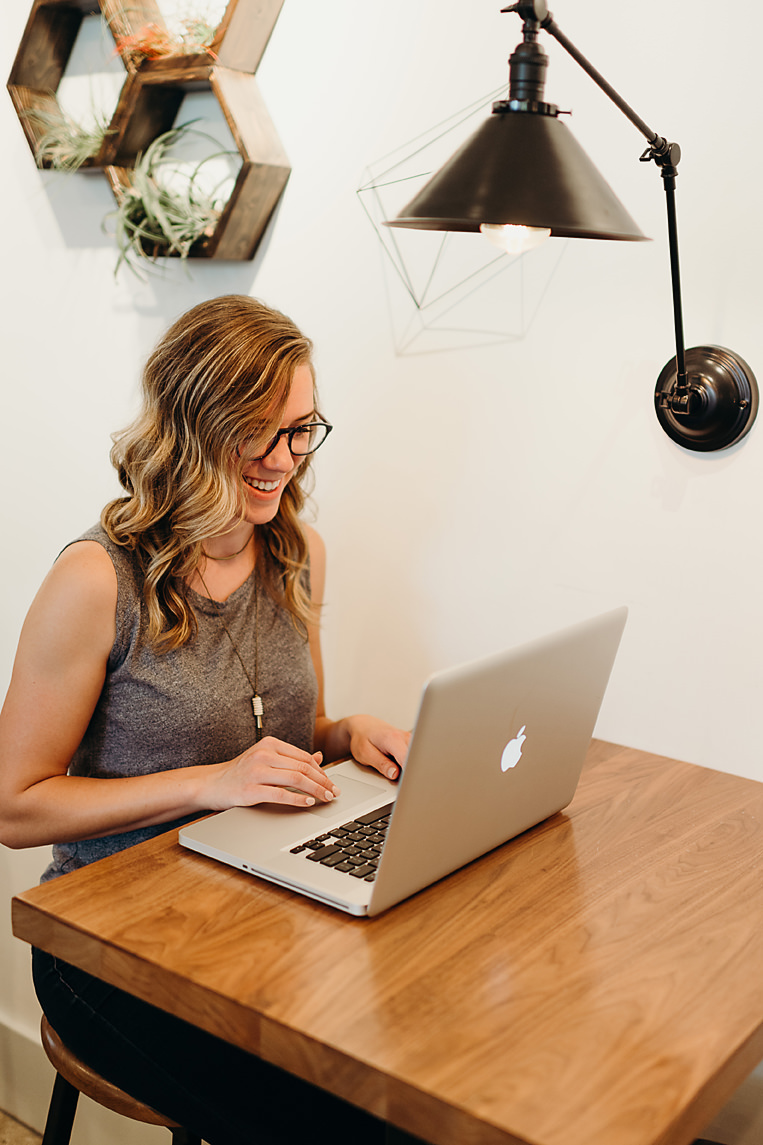 Graphic designer smiling and working on MacBook