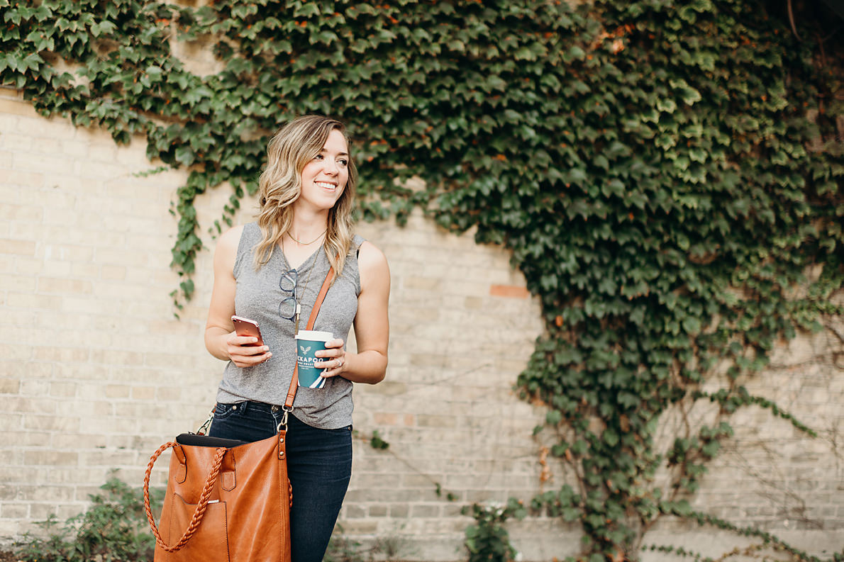 Busy small business owner holding phone and coffee