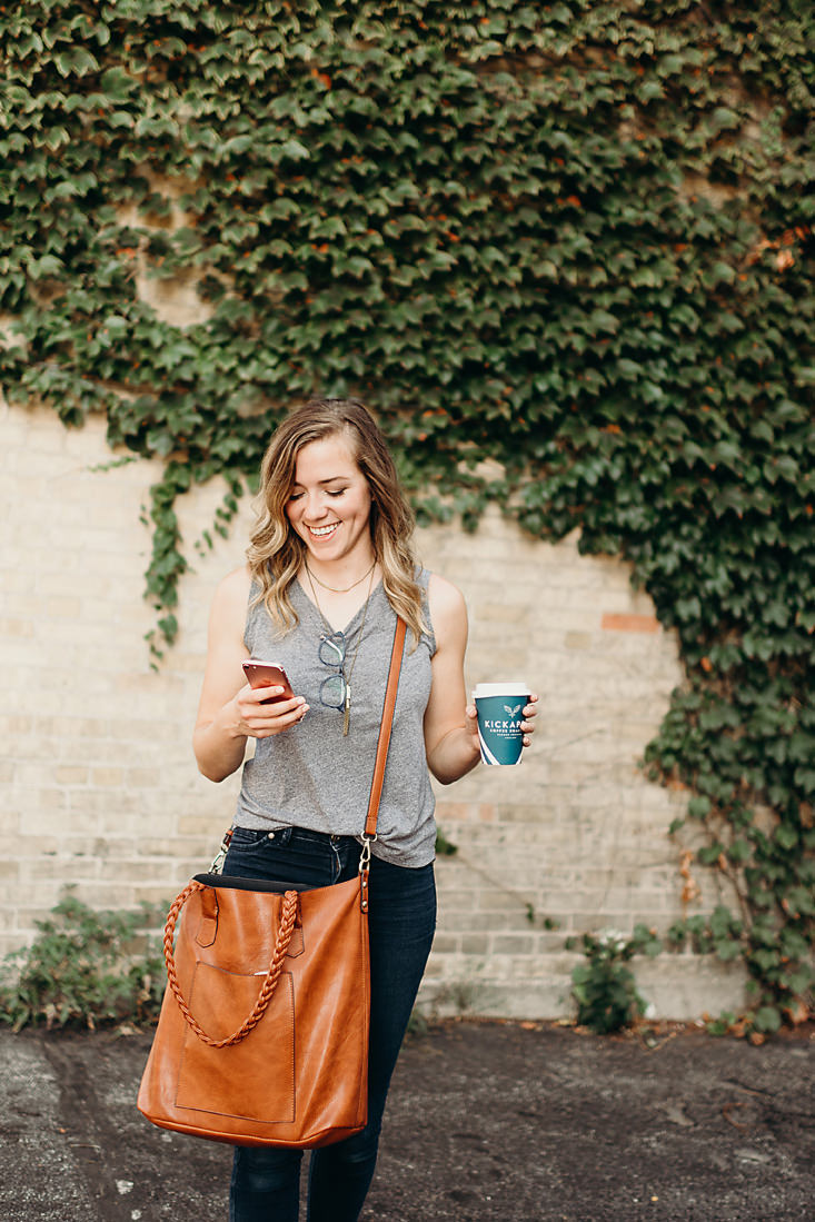 Small business owner holding coffee cup and checking messages