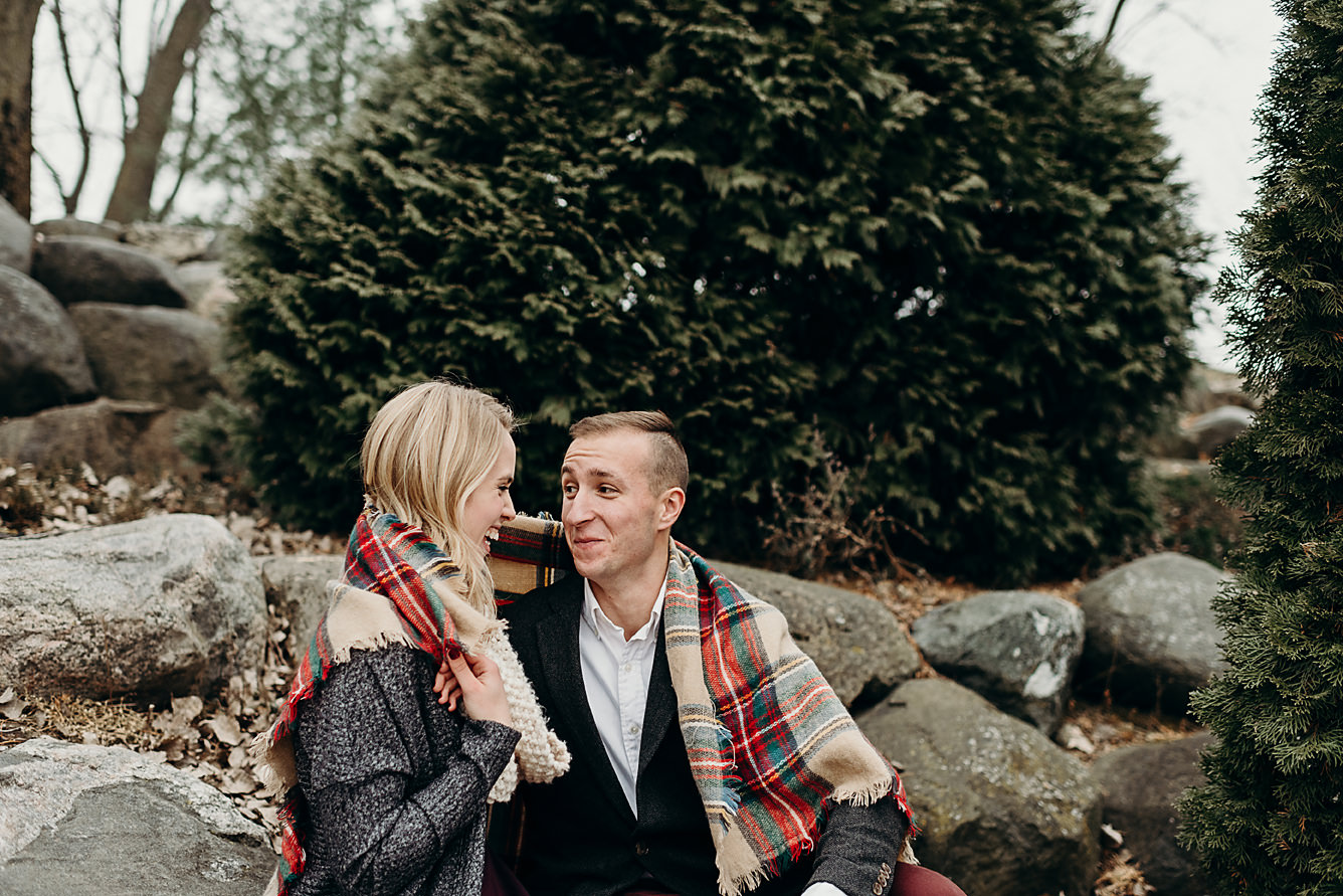 Engaged couple wrapped in a blanket
