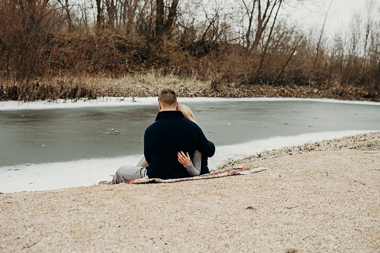 Engaged couple sitting on a blanket by a creek